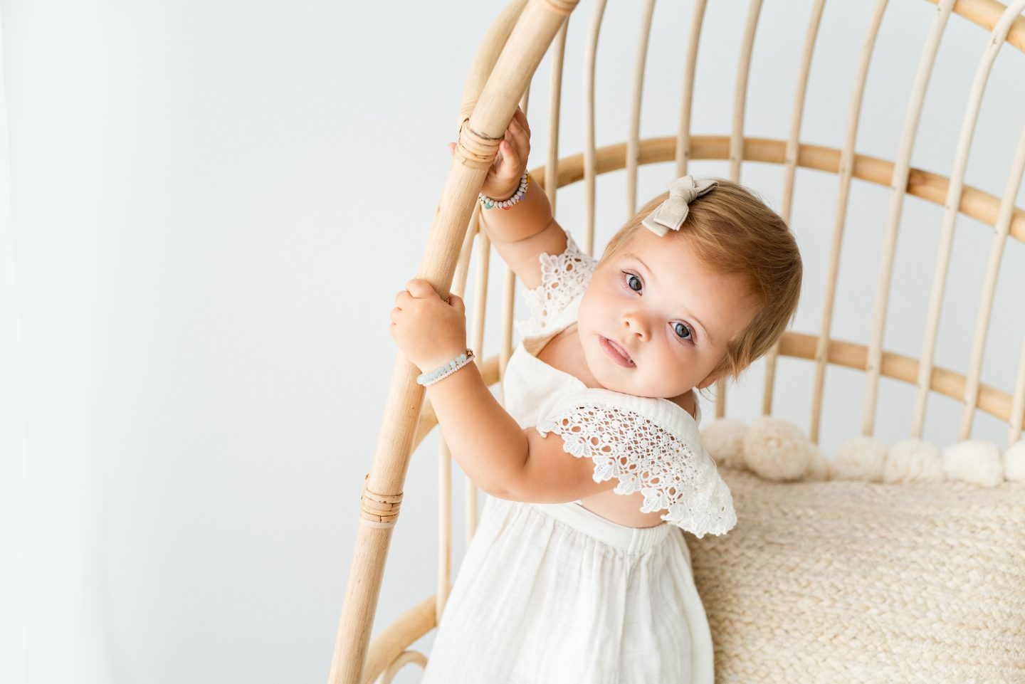 One Year Old Milestones by popular San Diego motherhood blog, Navy Grace: image of a baby girl wearing a white dress standing on a rattan chair.
