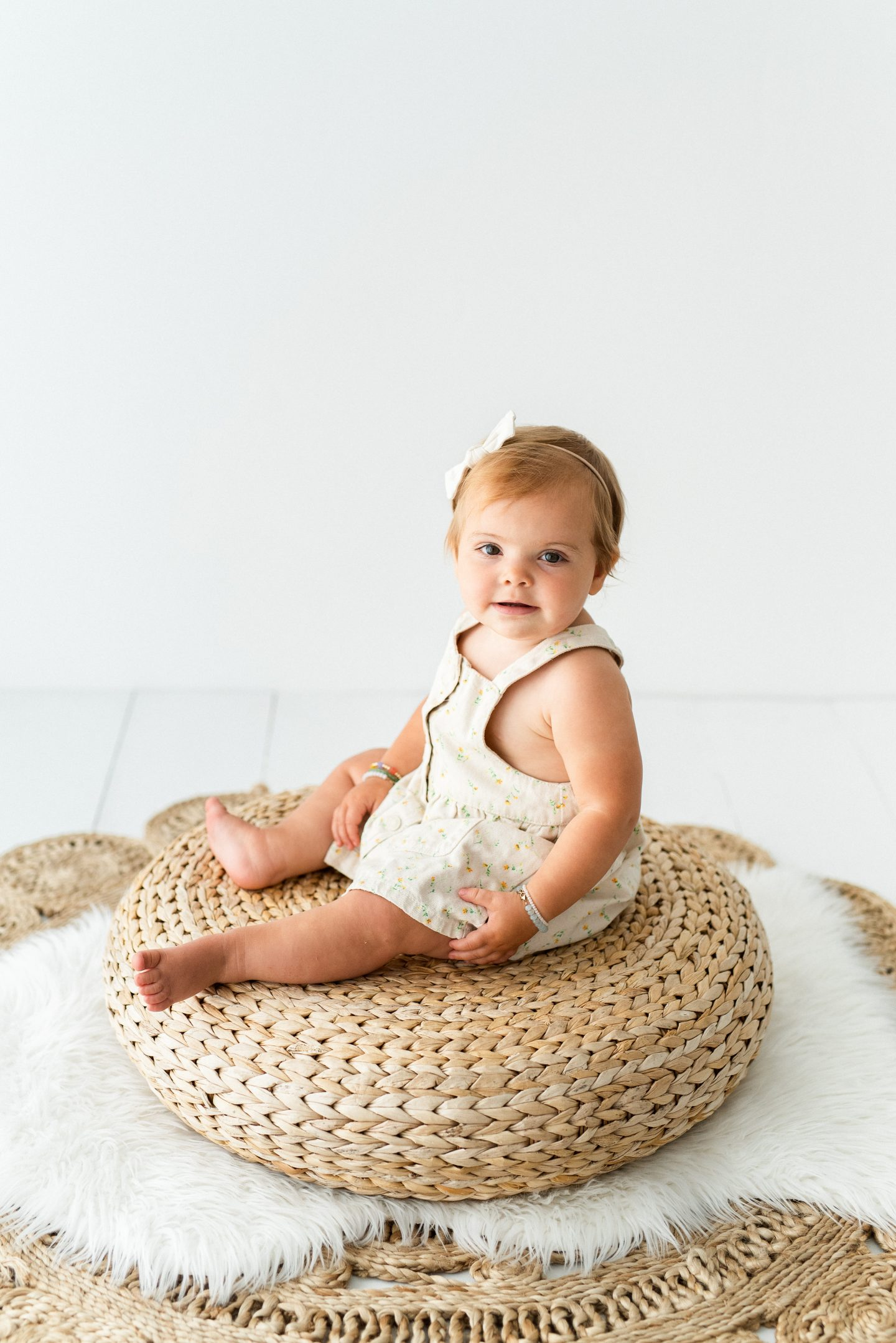 One Year Old Milestones by popular San Diego motherhood blog, Navy Grace: image of a baby girl wearing a floral print dress and sitting on a woven floor pillow.
