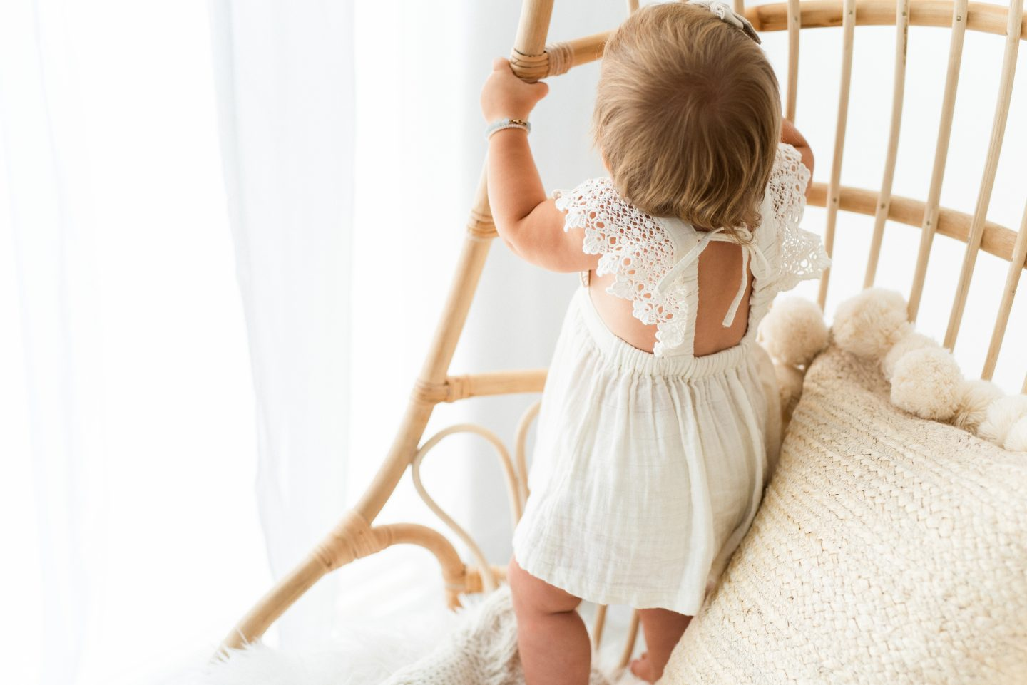 One Year Old Milestones by popular San Diego motherhood blog, Navy Grace: image of a baby girl wearing a white dress and standing on a rattan chair.