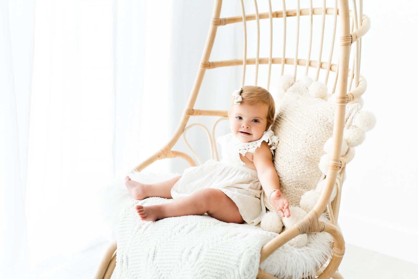 One Year Old Milestones by popular San Diego motherhood blog, Navy Grace: image of a baby girl wearing a white dress and sitting in a rattan chair.