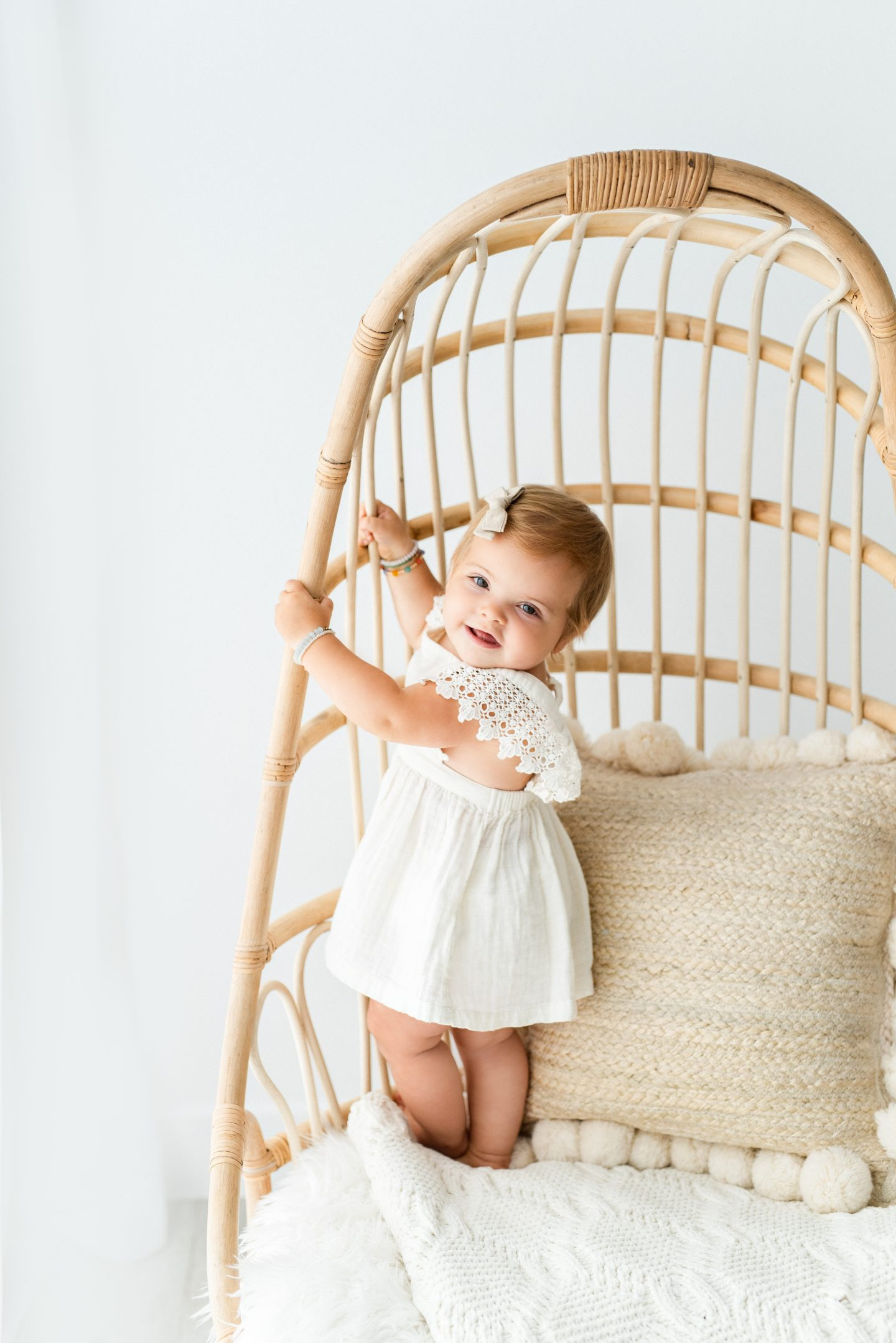 One Year Old Milestones by popular San Diego motherhood blog, Navy Grace: image of a baby girl wearing a white dress and standing in a rattan chair.