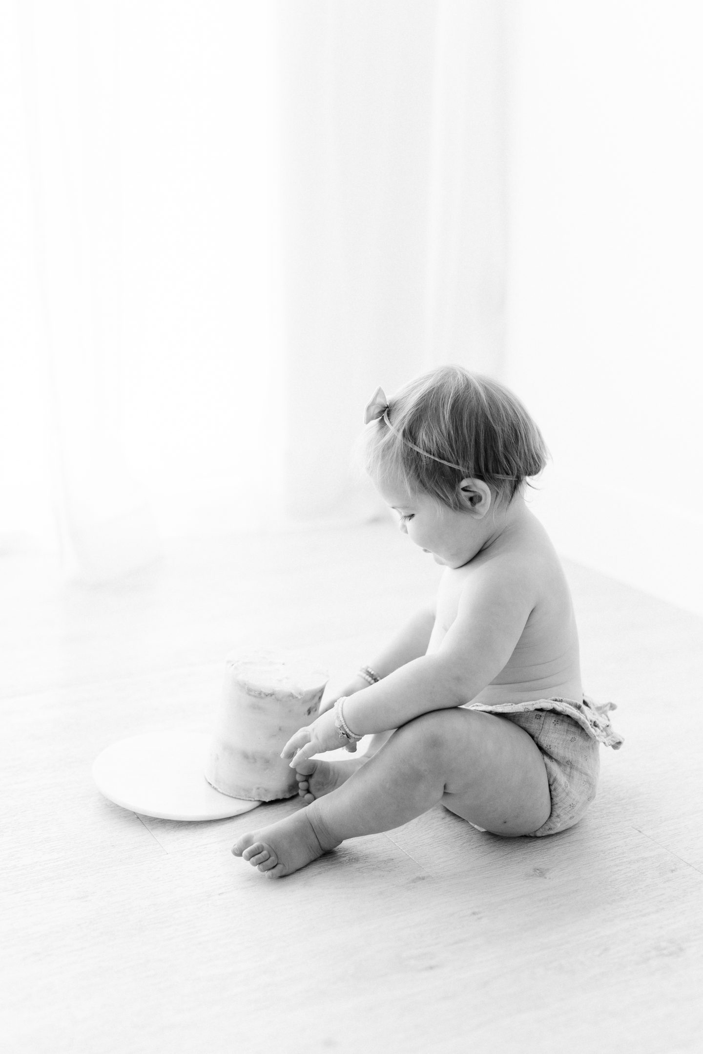 One Year Old Milestones by popular San Diego motherhood blog, Navy Grace: image of a baby girl eating a smash cake.