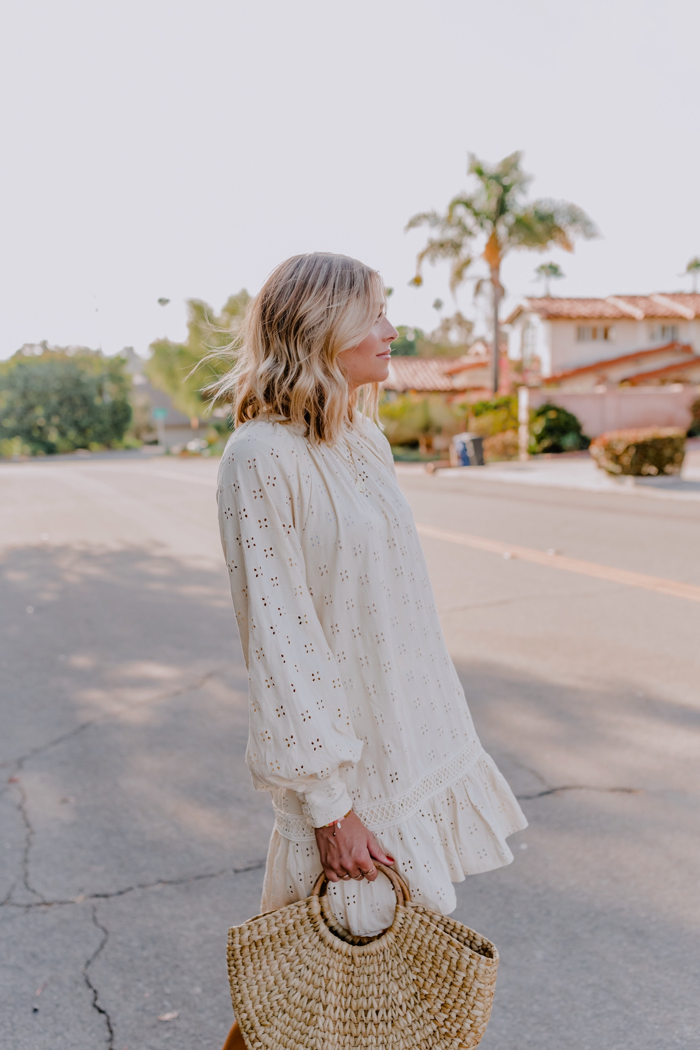 Summer Whites by popular San Diego fashion blog, Navy Grace: image of a woman walking outside on a street and wearing a ASOS  broderie long sleeve mini smock dress in cream, Sezane High Thomas Sandals, Gorjana Astrology Coin Necklace, and holding a Rhodes Mini Straw Tote Bag.