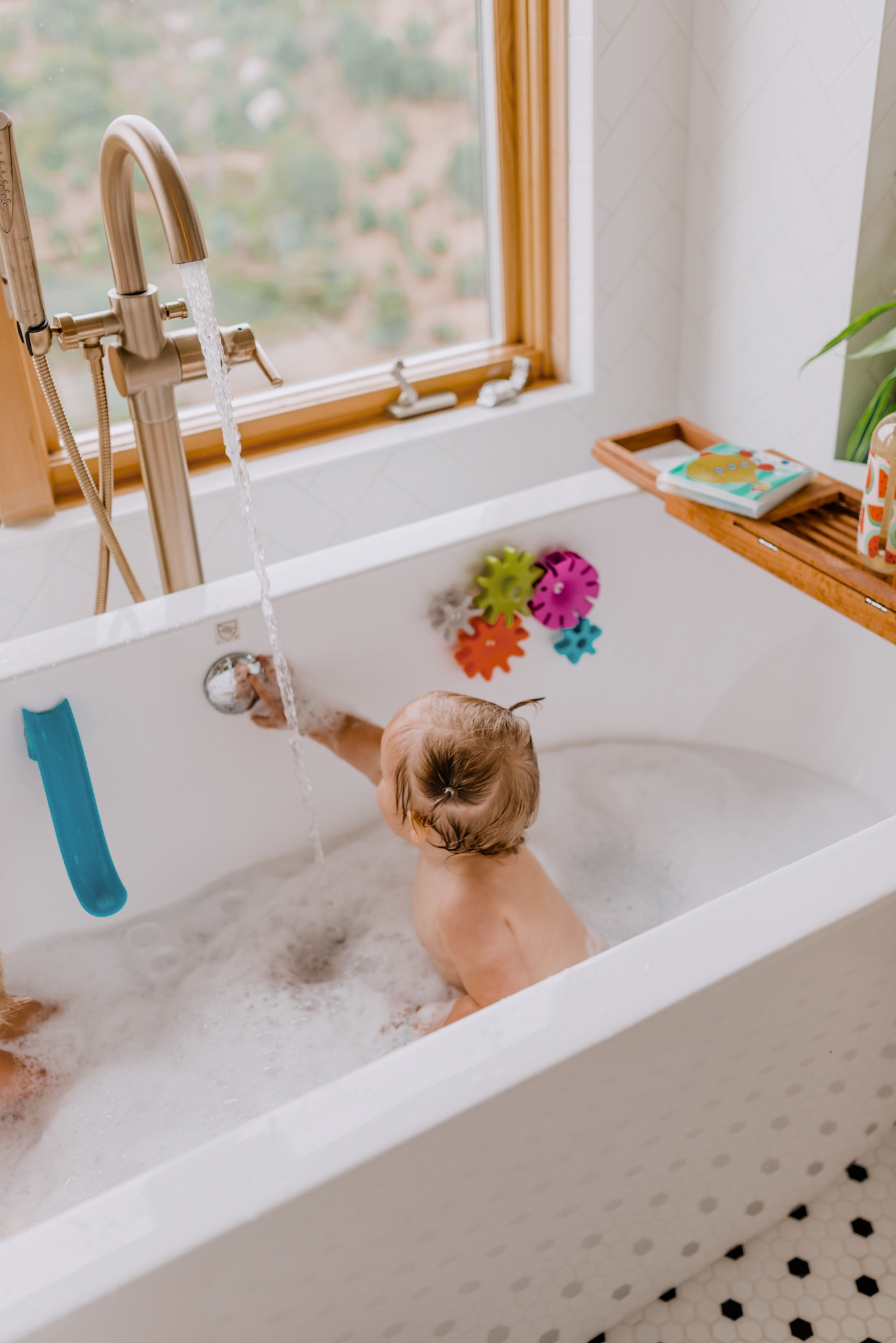 Baby Bath Toys by popular San Diego motherhood blog, Navy Grace: image of two kids sitting in the tub and taking a bubble bath while playing with various amazon bath toys.