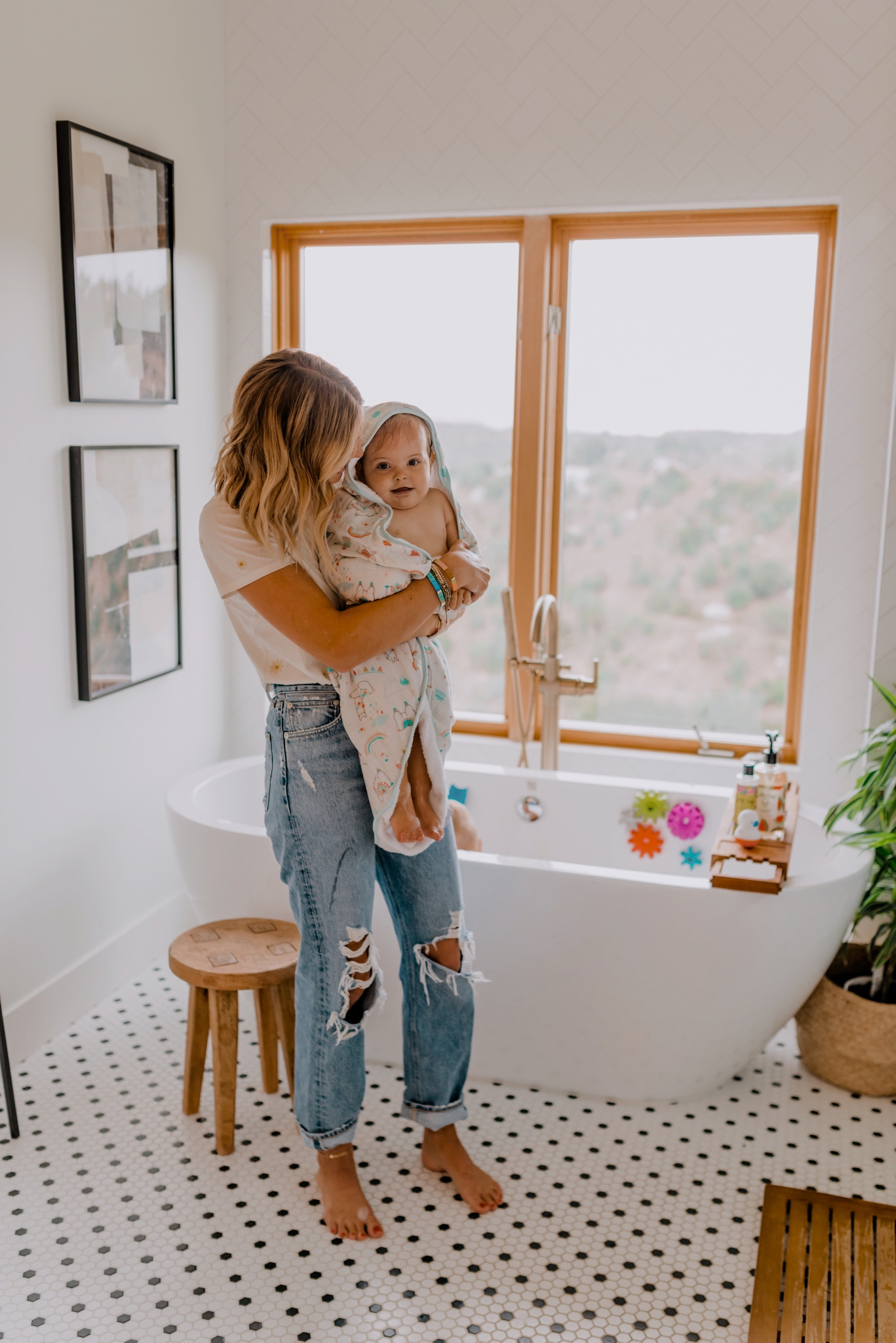 Baby Bath Toys by popular San Diego motherhood blog, Navy Grace: image of a mom holding her baby girl and wrapping her in a towel while she stands next to her her young son who's in the tub taking a bubble bath while playing with various amazon bath toys.