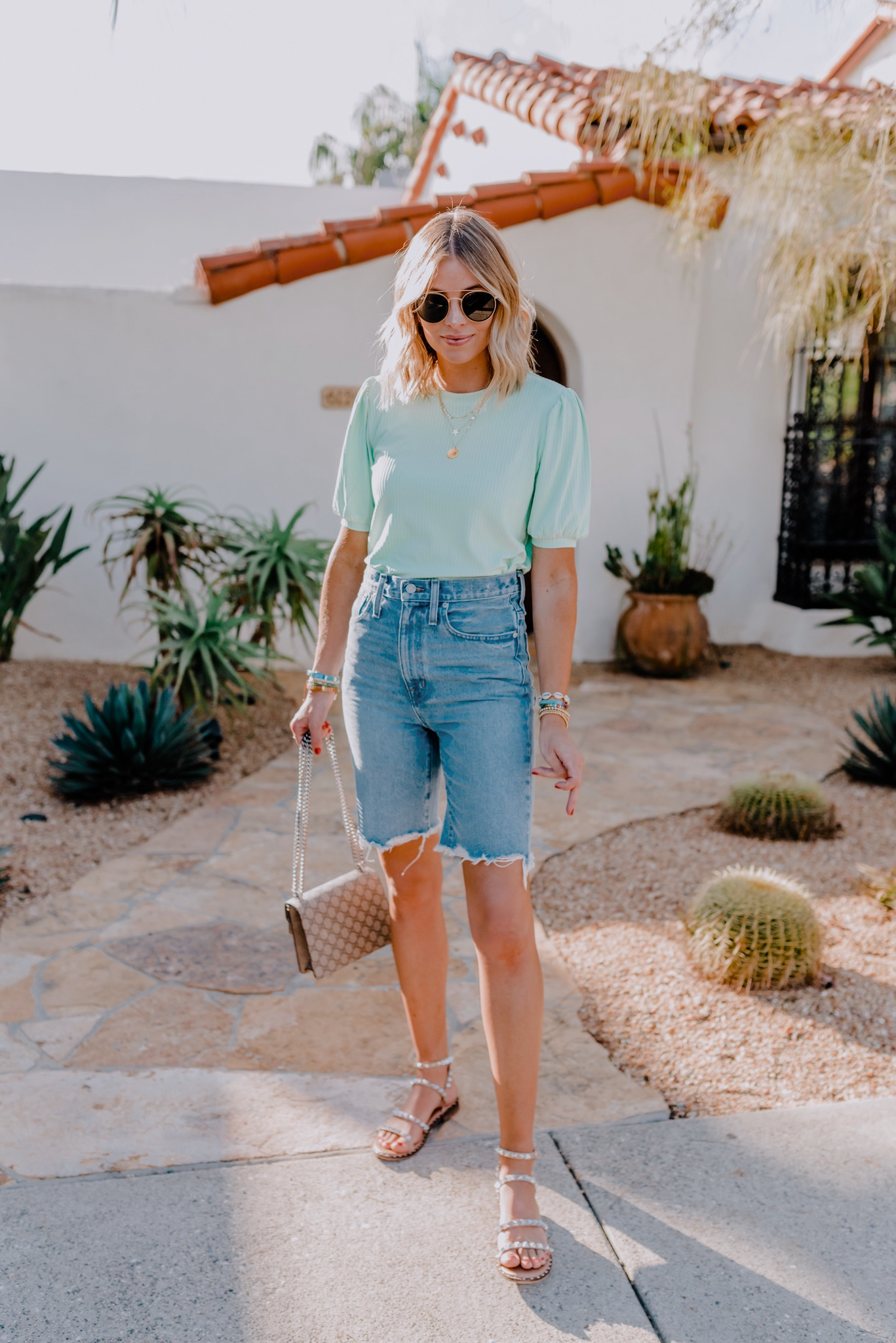 Summer Handbags by popular San Diego fashion blog, Navy Grace: image of a woman standing outside on a stone walkway and wearing a Asos Pieces ribbed top with puff sleeves in mint green, ShopBop Madewell High Rise Midi Length Jean Shorts, Nordstrom Transport Studded Strappy Sandal STEVE MADDEN, Ray-Ban sunglasses, and holding a Gucci Dionysus GG Supreme mini bag.