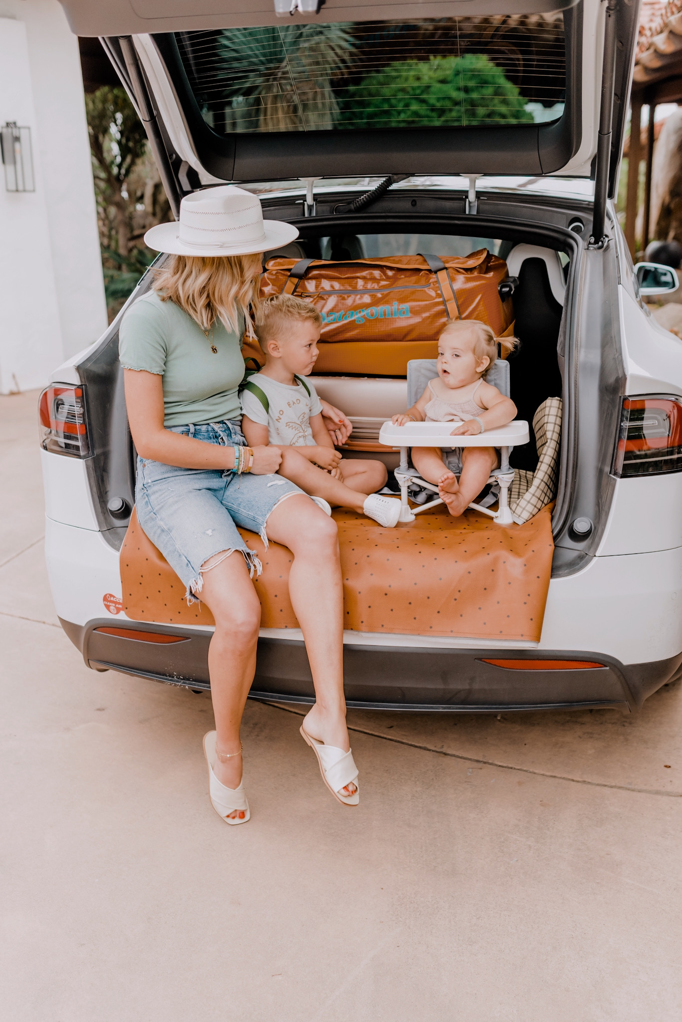 Family Travel by popular San Diego motherhood blog, Navy Grace: image of a mom sitting on a Gathre mat in the back of her car while holding on to her young son who is wearing a Nordstrom 'Mini Kånken' Water Resistant Backpack FJÄLLRÄVEN and standing next to a Nordstrom 40-Liter Rolling Duffle Bag PATAGONIA and his baby sister who is sitting in a Amazon Summer Infant Summer Pop 'n Sit Portable Booster Chair.