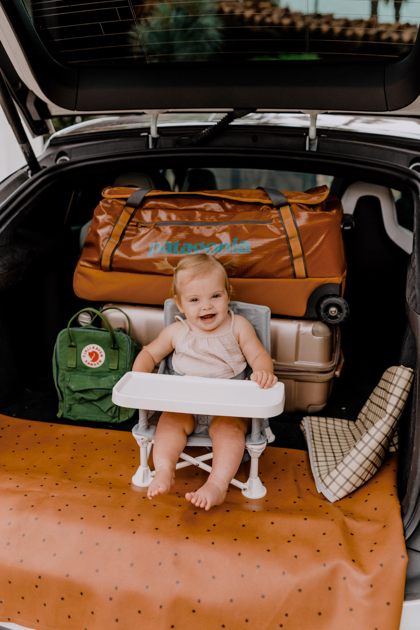 Family Travel by popular San Diego motherhood blog, Navy Grace: image of a baby girl sitting in a Amazon Summer Infant Summer Pop 'n Sit Portable Booster Chair net to a Gatrhe Mat, Patagonia rolling duffle bag, and 'Mini Kånken' Water Resistant Backpack FJÄLLRÄVEN in the back of a car.