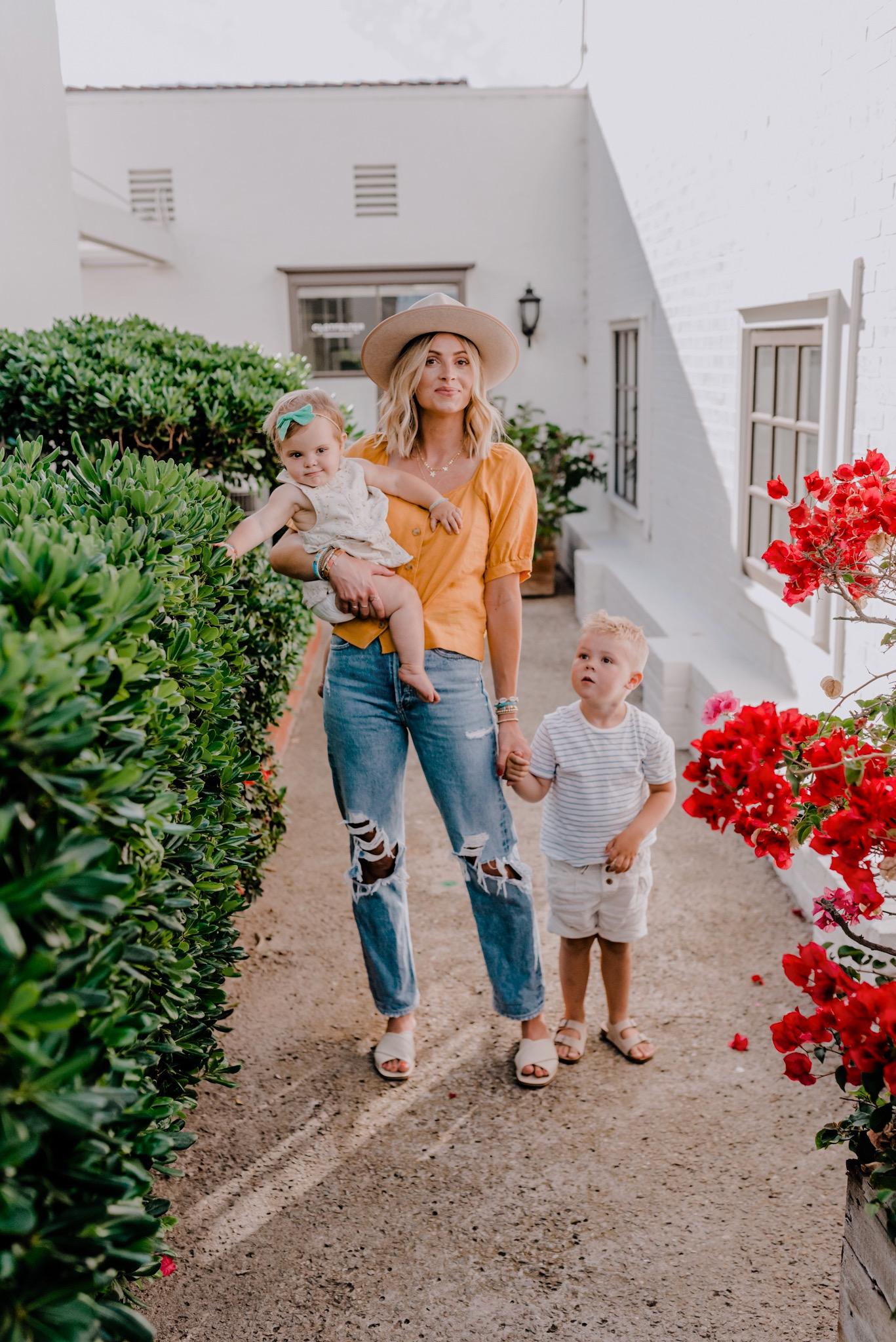 Summer Clothing by popular San Diego fashion blog, Navy Grace: image of a mom and her two kids standing outside by some red flower bushes and white brick building and wearing a Everlane The Linen Puff-Sleeve Top, Agolde 90s Mid Rise Loose Fit, Everlane The Day Crossover Sandal, Amazon Gigi Pip Monroe Oatmeal - Women's Rancher Hat, Little Poppy bow, and H&M faux suede sandals.