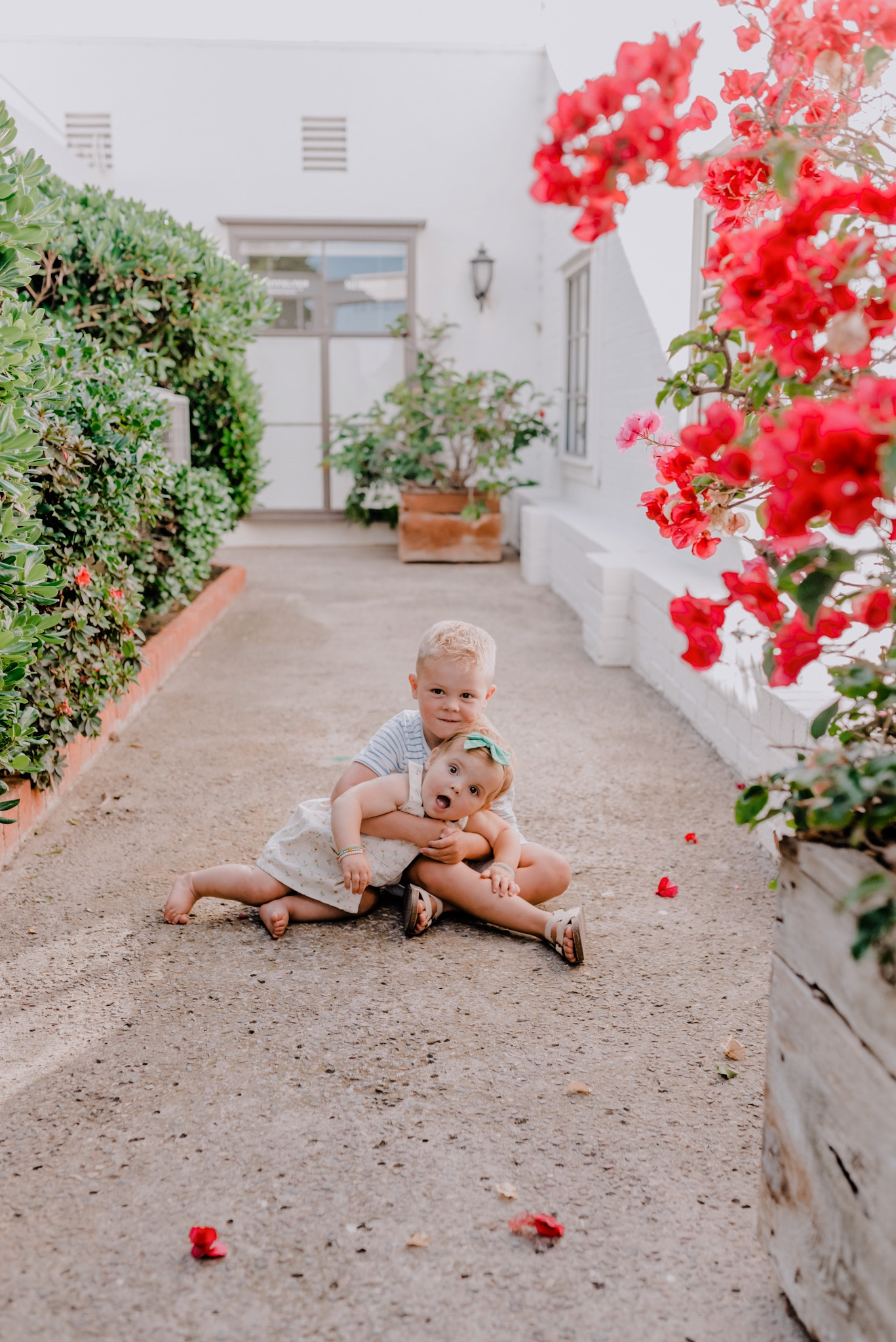 Summer Clothing by popular San Diego fashion blog, Navy Grace: image of a little boy and girl sitting outside next to a red flowering bush and white brick building and wearing a Little Poppy bow and H&M faux suede sandals.