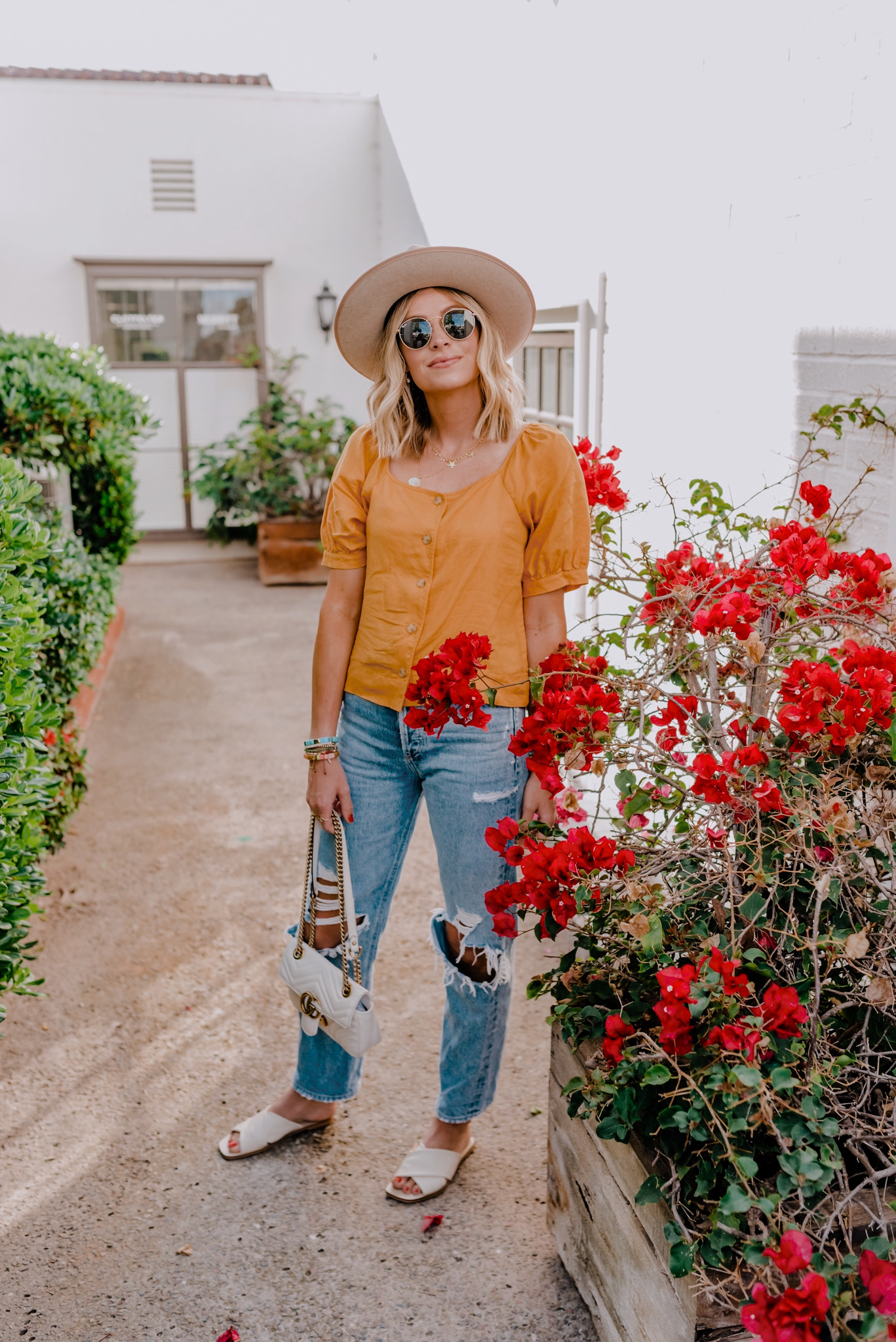 Summer Clothing by popular San Diego fashion blog, Navy Grace: image of a woman standing outside by some red flower bushes and white brick building and wearing a Everlane The Linen Puff-Sleeve Top, Agolde 90s Mid Rise Loose Fit, Everlane The Day Crossover Sandal, and Amazon Gigi Pip Monroe Oatmeal - Women's Rancher Hat