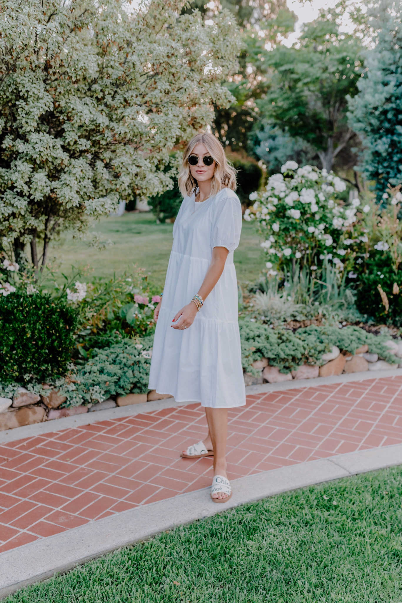 Nordstrom Anniversary Sale by popular San Diego fashion blog, Navy Grace: image of a woman wearing a Everlane The Tiered Cotton Dress, Nordstrom Logo Slide Sandal CHLOÉ, and Ray-Ban sunglasses.