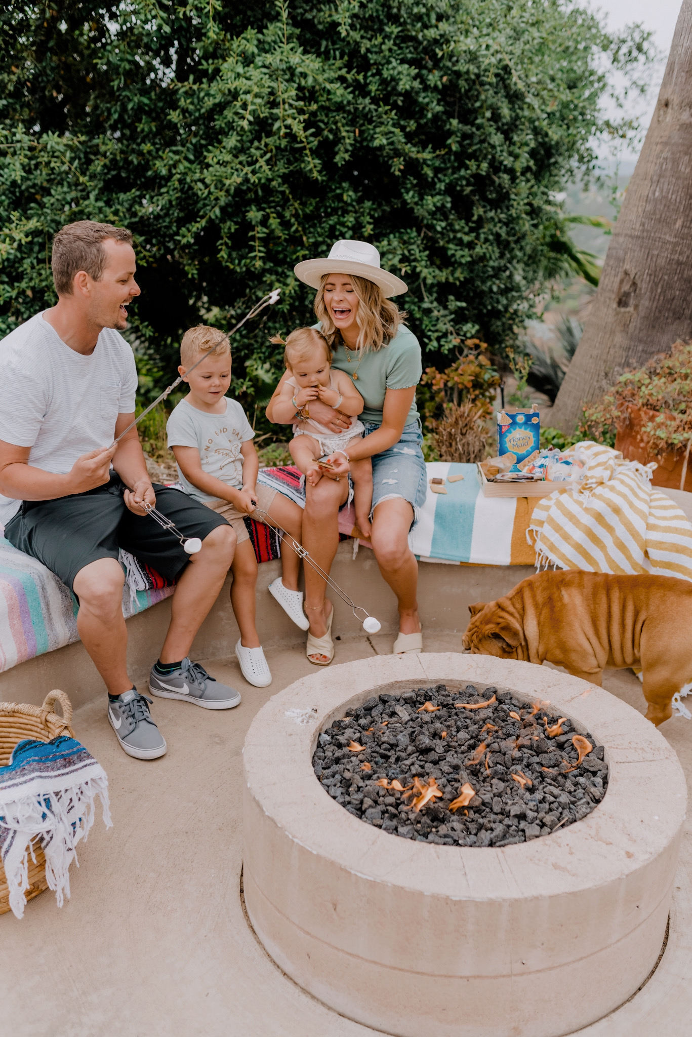 Outdoor Essentials by popular San Diego lifestyle blog, Navy Grace: image of a family sitting on Mexican blankets around a fire pit and roasting marshmallows.
