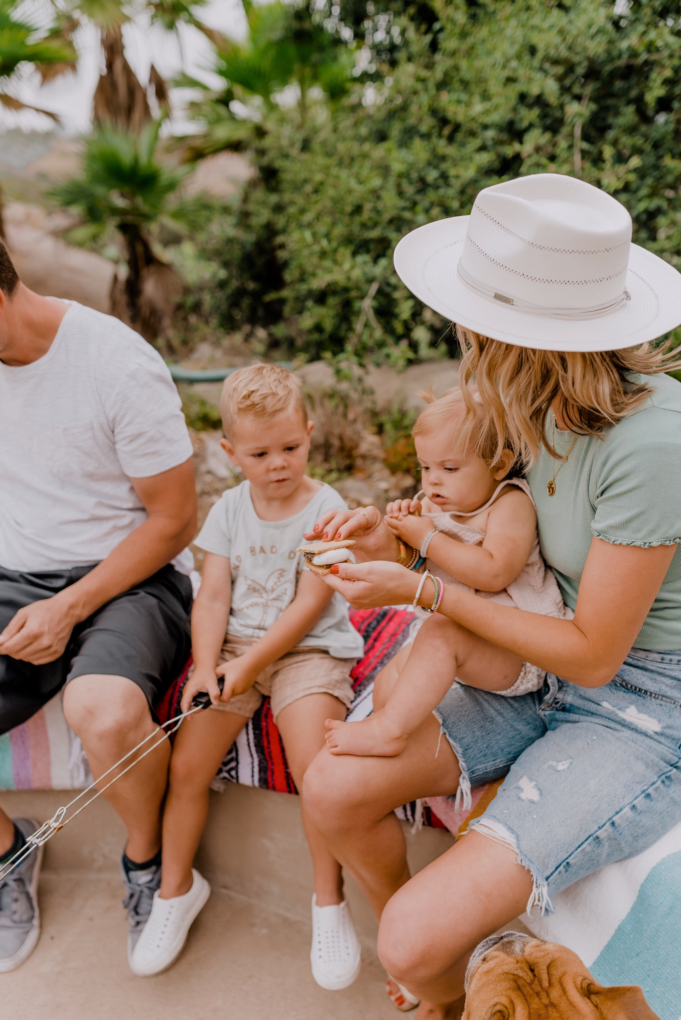 Outdoor Essentials by popular San Diego lifestyle blog, Navy Grace: image of a family eating s'mores.