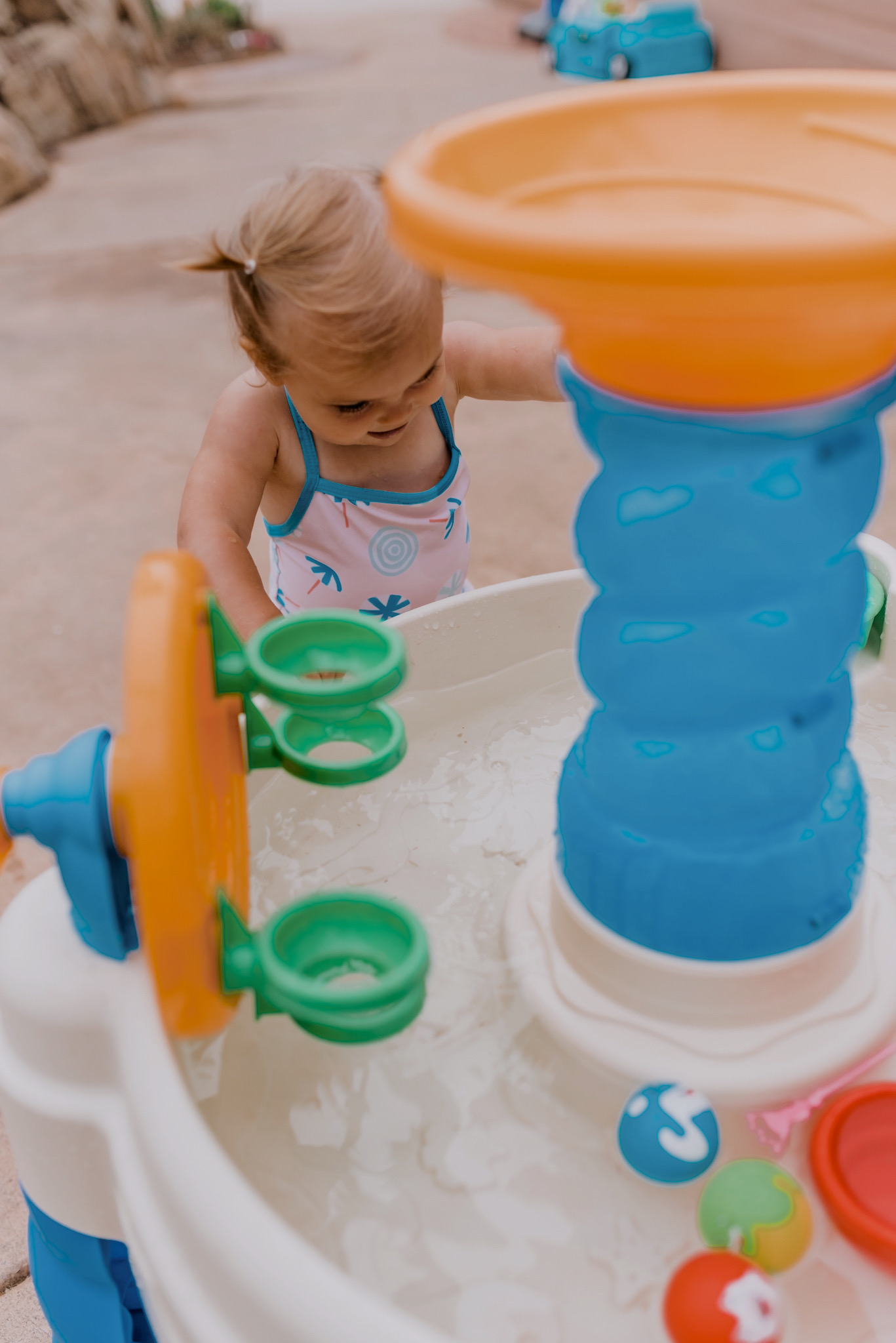 18 SUPER FUN OUTDOOR ACTIVITIES FOR YOUR FAMILY THIS SUMMER featured by top San Diego lifestyle blogger, Navy Grace | Family Outdoor Activities by popular San Diego lifestyle blog, Navy Grace: image of a baby girl playing with a water table.