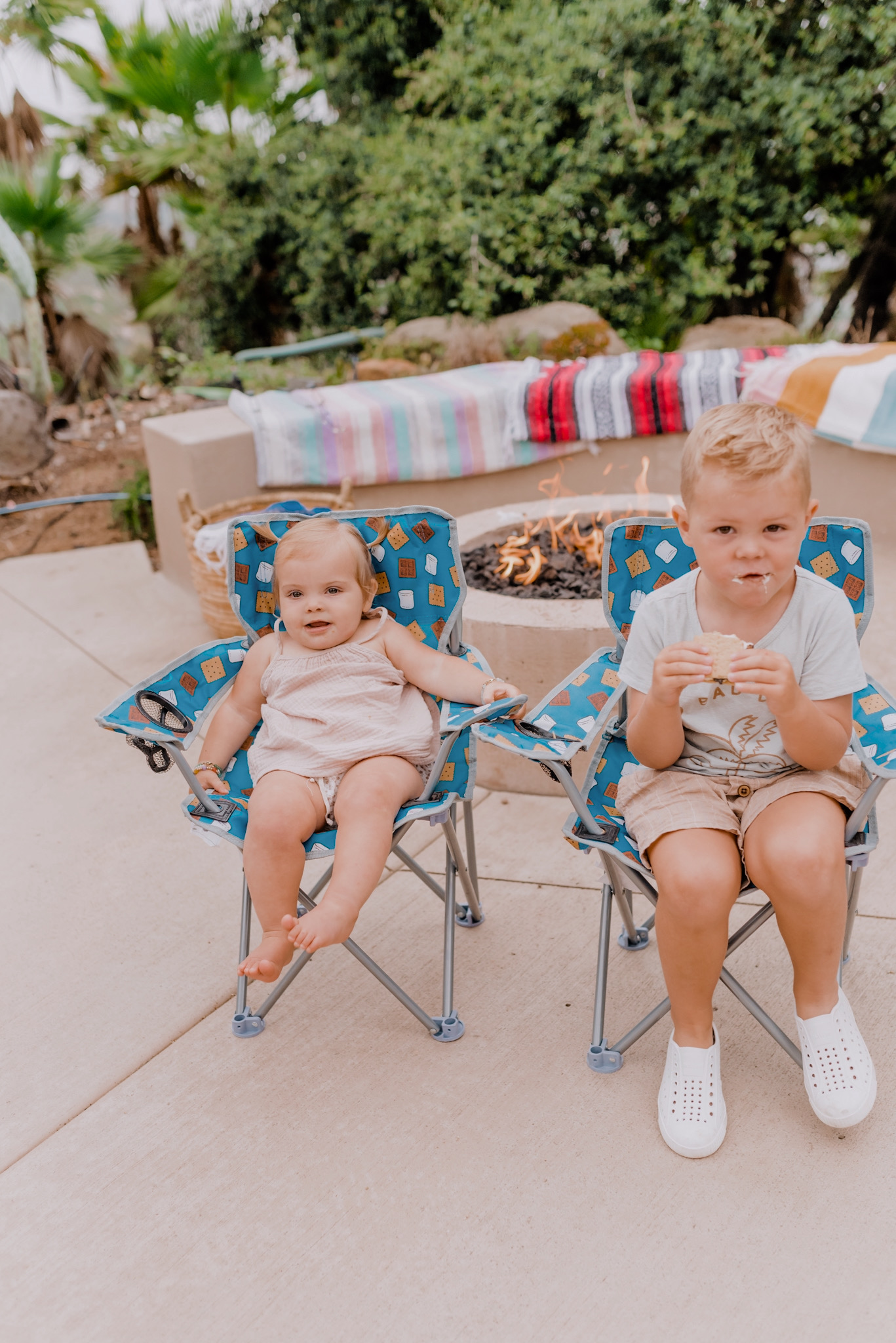 Outdoor Essentials by popular San Diego lifestyle blog, Navy Grace: image of two kids sitting in folding camping chairs and eating S'mores.