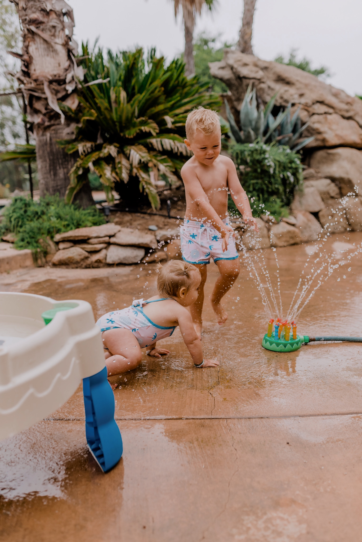 18 SUPER FUN OUTDOOR ACTIVITIES FOR YOUR FAMILY THIS SUMMER featured by top San Diego lifestyle blogger, Navy Grace | Family Outdoor Activities by popular San Diego lifestyle blog, Navy Grace: image of a young boy and baby girl playing with a Melissa & Doug Splash Patrol Sprinkler.