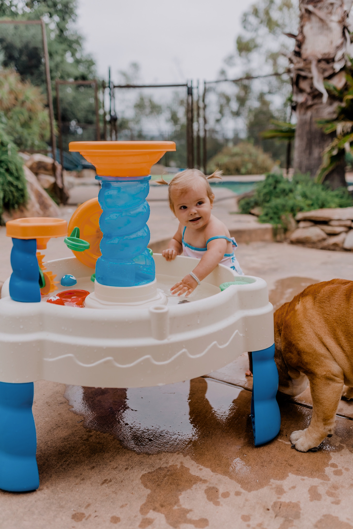 18 SUPER FUN OUTDOOR ACTIVITIES FOR YOUR FAMILY THIS SUMMER featured by top San Diego lifestyle blogger, Navy Grace | Family Outdoor Activities by popular San Diego lifestyle blog, Navy Grace: image of a baby girl playing at a water table.