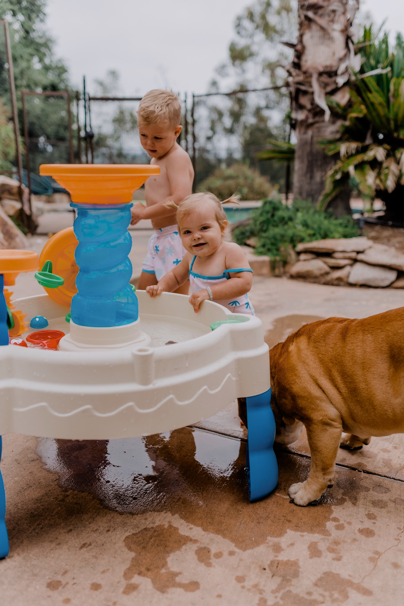 18 SUPER FUN OUTDOOR ACTIVITIES FOR YOUR FAMILY THIS SUMMER featured by top San Diego lifestyle blogger, Navy Grace | Family Outdoor Activities by popular San Diego lifestyle blog, Navy Grace: image of a young boy and baby girl playing with a water table.