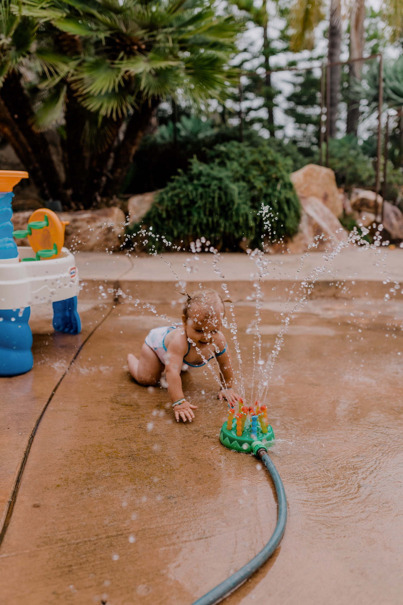 18 SUPER FUN OUTDOOR ACTIVITIES FOR YOUR FAMILY THIS SUMMER featured by top San Diego lifestyle blogger, Navy Grace | Family Outdoor Activities by popular San Diego lifestyle blog, Navy Grace: image of a baby girl playing with a Melissa & Doug Splash Patrol Sprinkler.