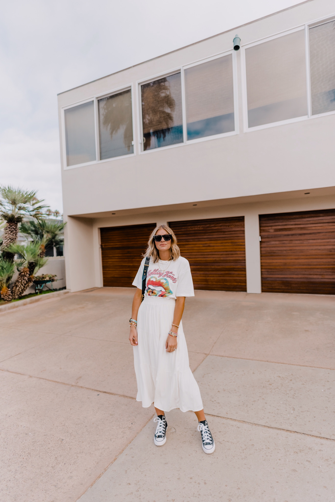 Amazon Favorites by popular San Diego life and style blog, Navy Grace: image of a woman wearing a Free People Rolling Stones Tie Dye Tongue Tee, And Other Stories Smocked Waist Tiered Midi Skirt, Nordstrom Mosanana Square Cateye Sunglasses for Women, and black Converse high tops.