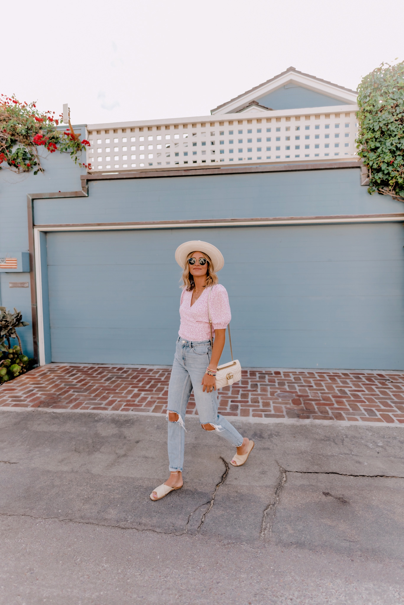 Summer Clothing by popular San Diego fashion blog, Navy Grace: image of a woman standing in front of a blue building and wearing a and other stories Printed Puff Sleeve Wrap Top, TopShop Bleach Wash Double Rip Mom Tapered Jeans, Gigi Pip ARLO CREAM BAND - STRAW TEARDROP FEDORA, Everlane The Day Crossover Sandal, and holding a Gucci Small Matelassé Leather Shoulder Bag.