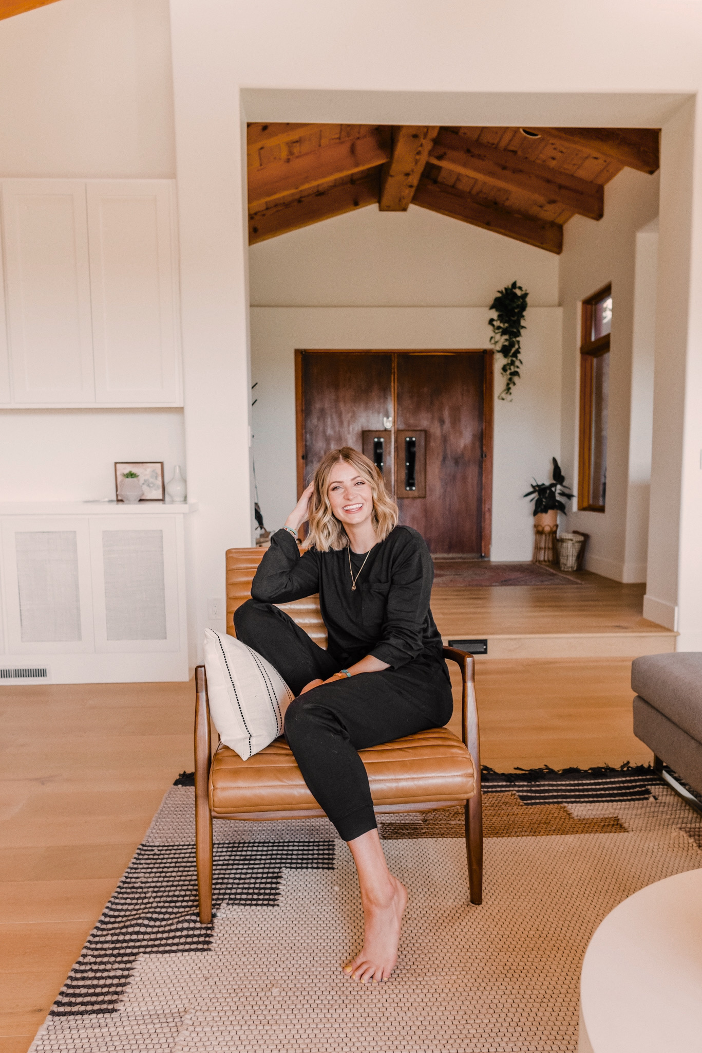 Nordstrom Anniversary Sale by popular San Diego fashion blog, Navy Grace: image of a woman sitting in a leather armchair and wearing a black loungewear set.