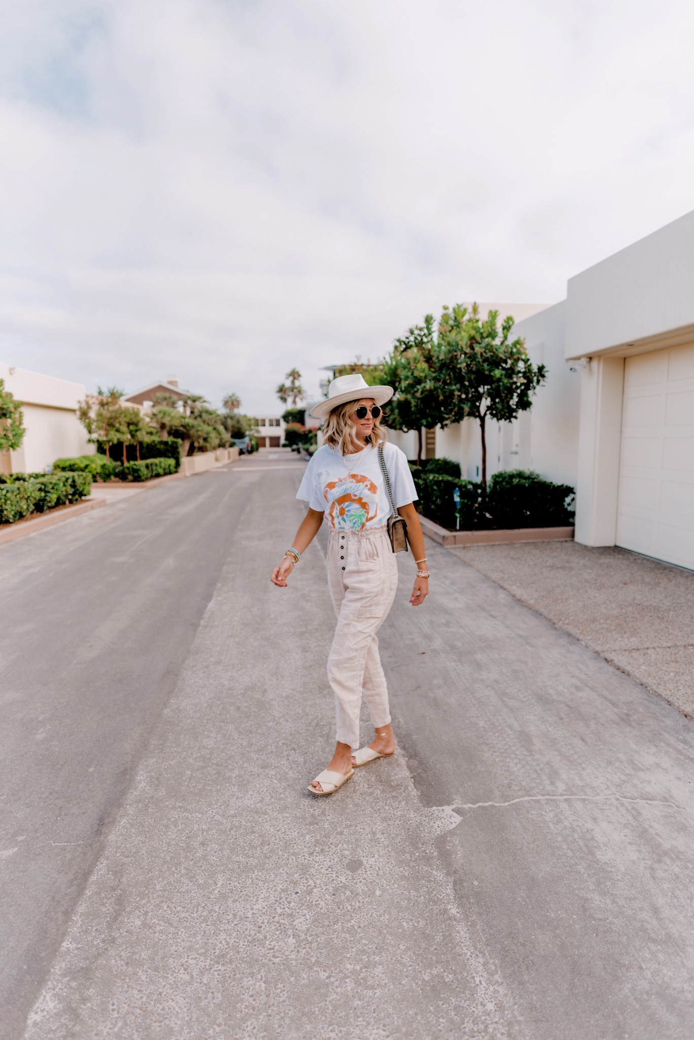 Graphic Tees by popular San Diego fashion blog, Navy Grace: image of a woman wearing a pair of Anthropologie Linen Utility Pants, Everlane The Day Crossover Sandal, Gigi Pip ARLO CREAM BAND - STRAW TEARDROP FEDORA, Gucci Dionysus GG Supreme mini bag, Ray-Ban sunglasses, and a Free People Beach Boys Tee.