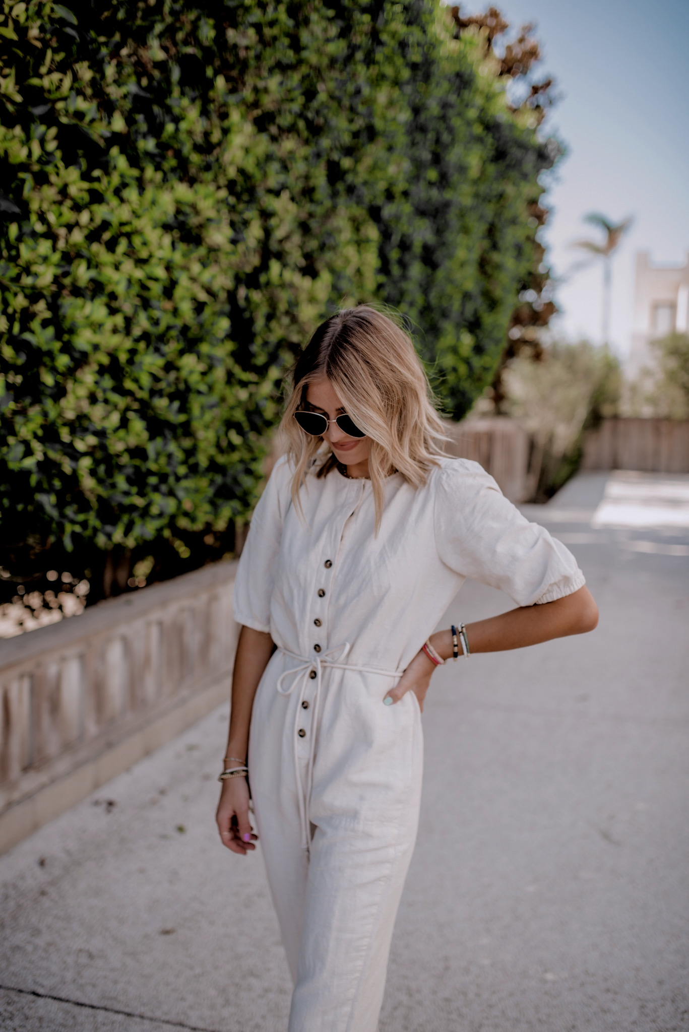 Fall Clothing by popular San Diego fashion blog, Navy Grace: image of a woman walking outside and wearing a Madewell Linen-Blend Puff-Sleeve Tassel-Tie Jumpsuit, Loeffler Randall Daphne Knot Flat Sandals, Le Specs Echo Sunglasses, and holding a Small Faye Leather Crossbody Bag CHLOÉ.