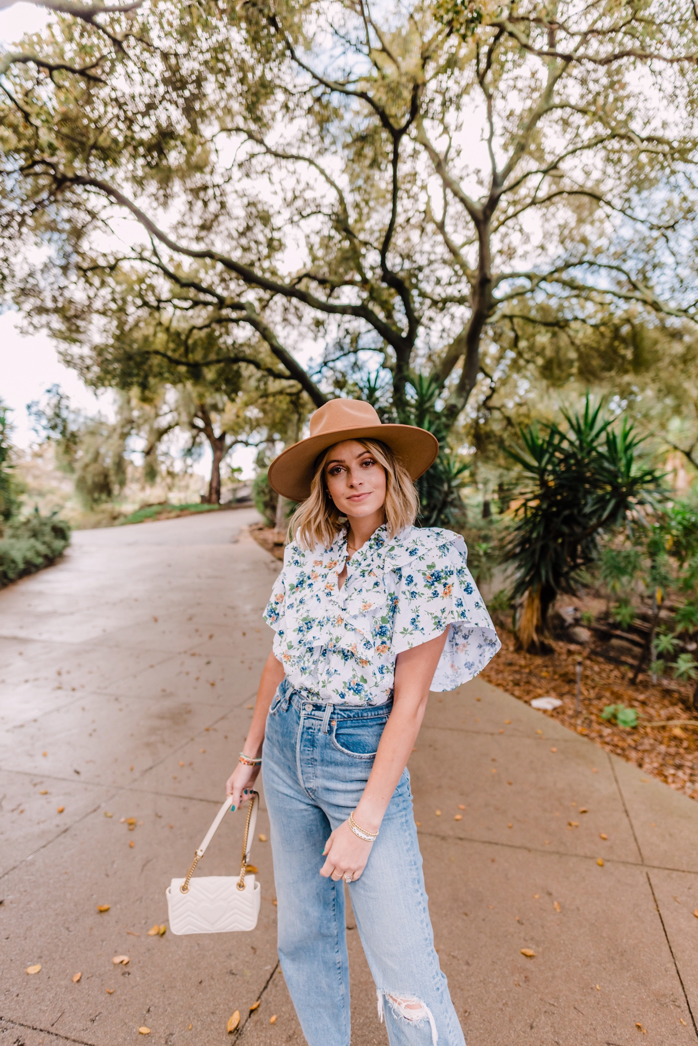 Nordstrom Anniversary Sale by popular San Diego fashion blog, Navy Grace: image of a woman standing outside and wearing a floral top, brown fedora hat, and high waist distressed denim while holding a Gucci purse.