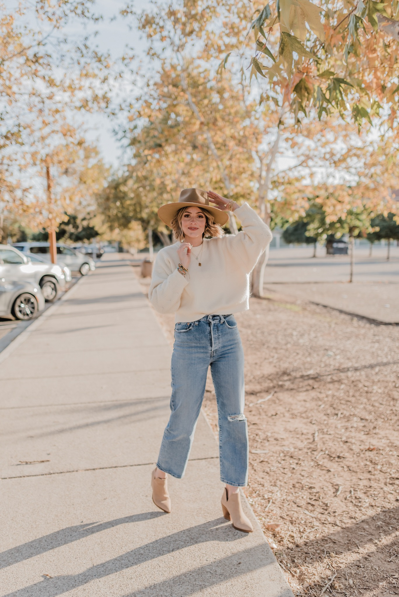 Nordstrom Anniversary Sale by popular San Diego fashion blog, Navy Grace: image of a woman wearing cropped distressed denim, suede ankle boots, a tan mock neck sweater, and felt fedora.