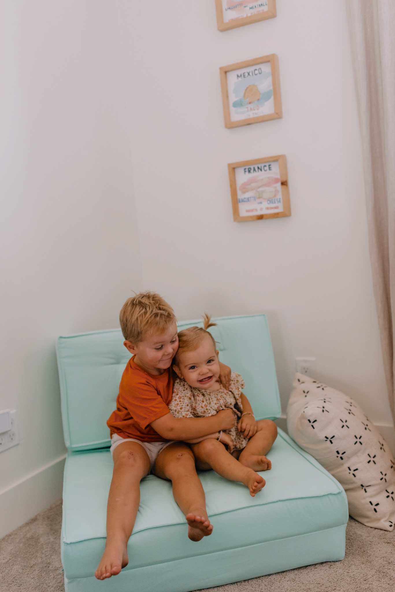 Walmart Decor by popular San Diego life and style blog, Navy Grace: image of a young boy and girl sitting together on a blue chair next to some framed world country prints.