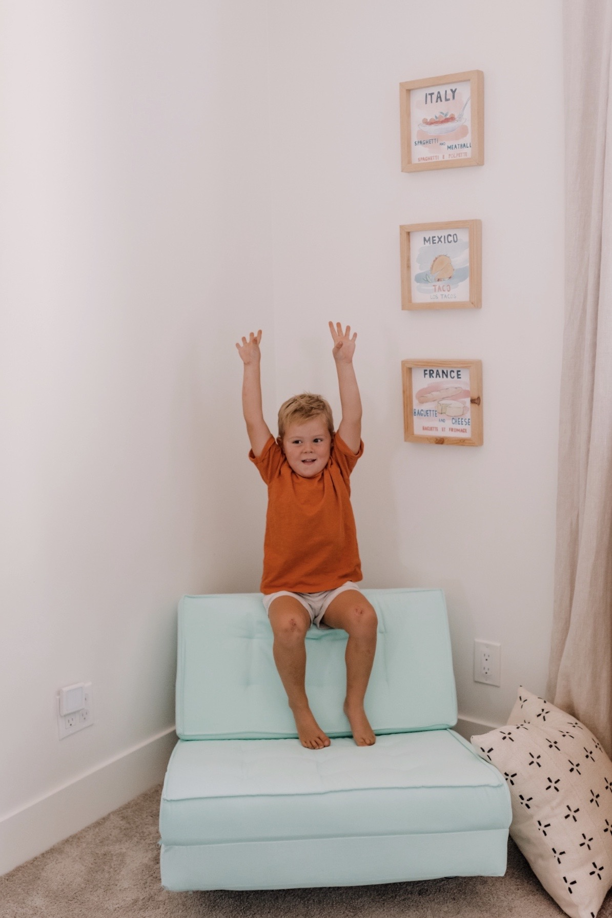 Walmart Decor by popular San Diego life and style blog, Navy Grace: image of a young boy siting on a blue chair next to some framed world country prints.