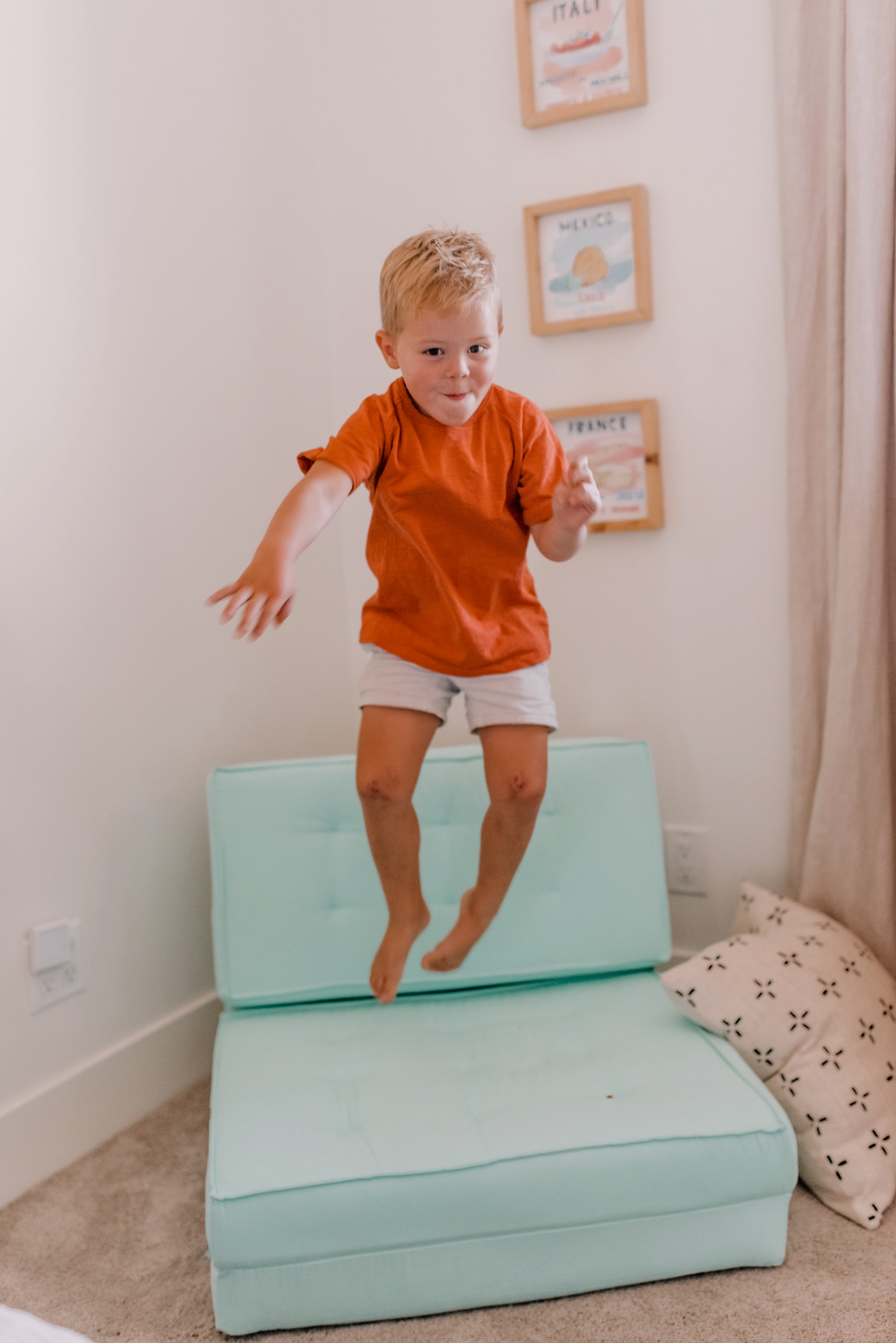 Walmart Decor by popular San Diego life and style blog, Navy Grace: image of a young boy jumping on a blue chair next to some framed world country prints.