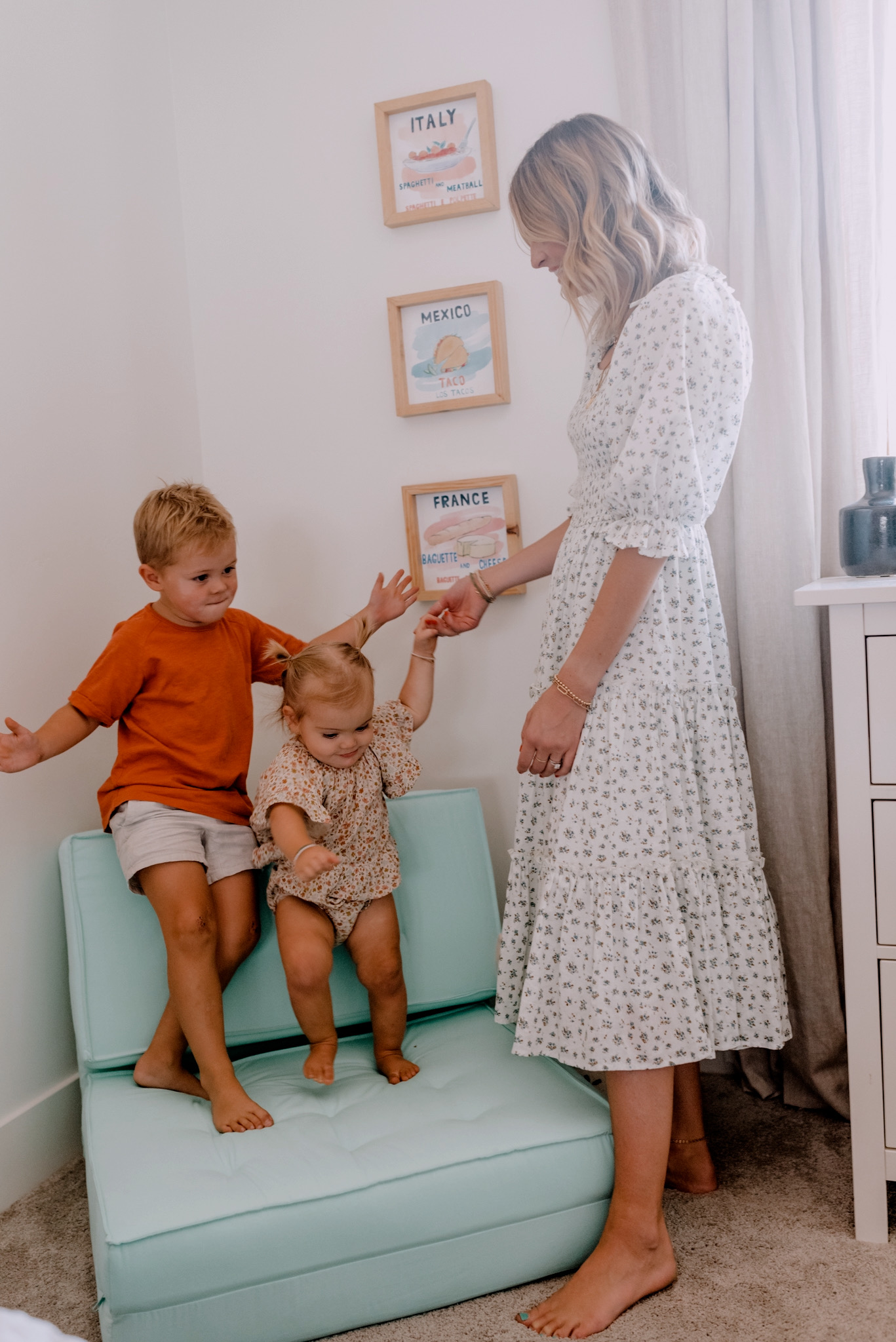 Walmart Decor by popular San Diego life and style blog, Navy Grace: image of a mom standing next to a young boy and girl standing together on a blue chair next to some framed world country prints.