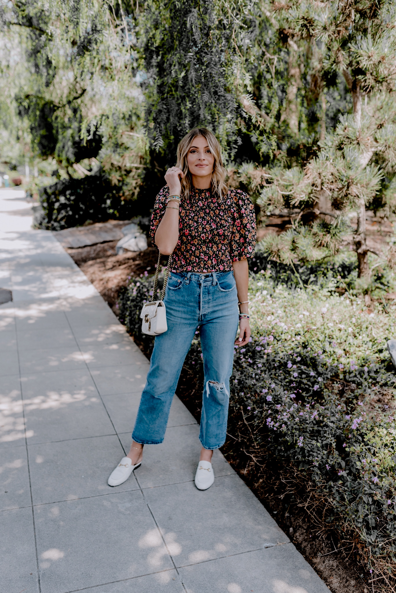Labor Day Sales by popular San Diego fashion blog, Navy Grace: image of a woman wearing a H&M Puff-sleeved Smocked Blouse, Urban Outiftters Levi's Ribcage Straight Jean, Nordstrom Princetown Loafer Mule GUCCI, and Nordstrom Small Matelassé Leather Shoulder Bag GUCCI.