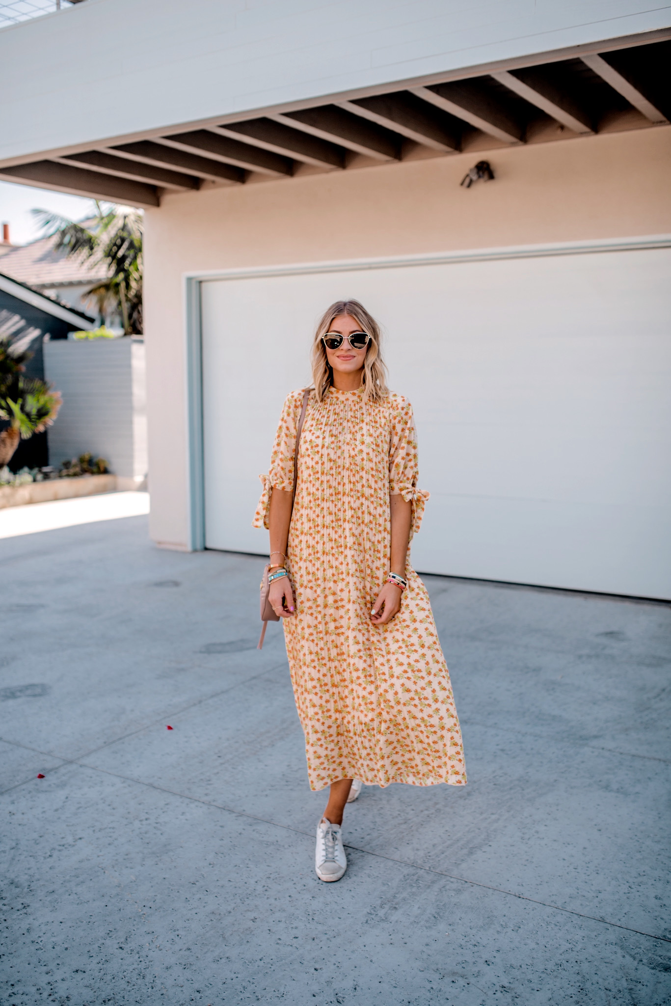 Fall Sneakers for Women by popular San Diego fashion blog, Navy Grace: image of a woman standing in front of a garage door and wearing a ASOS pleated trapeze midi dress with tie sleeves in ditsy floral print, Golden Goose sneakers, Le Specs Echo Sunglasses, and holding a Gucci purse.
