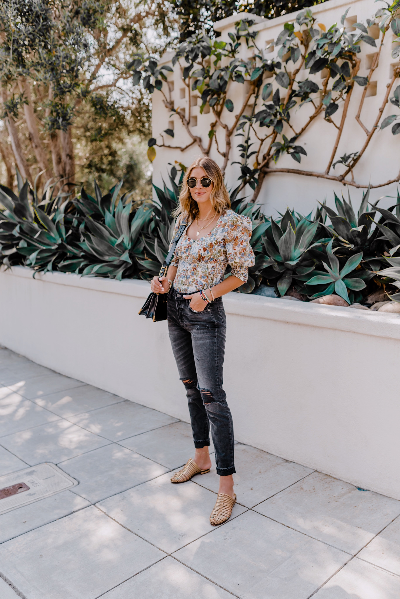 Fall Tops by popular San Diego fashion blog, Navy Grace: image of a woman standing outside by a white stucco wall and wearing a Anthropologie Amiens Puff-Sleeved Buttondown, Revolve Levi's 501 Skinny jeans, GLORIA slide mules, and Prada Cahier shoulder bag.