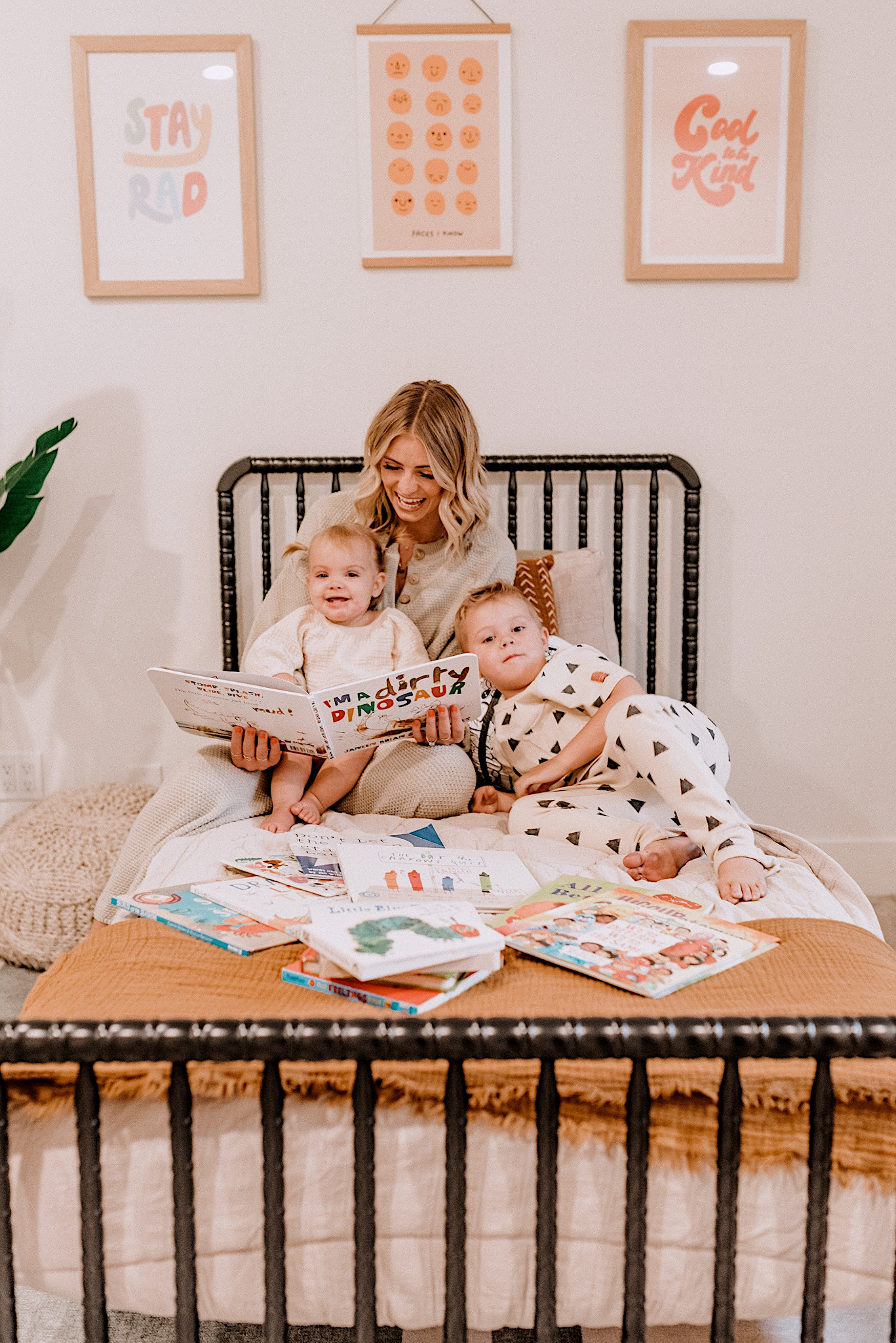 Best Children's Books by popular San Diego motherhood blog, Navy Grace: image of a mom sitting on a Jenny Lind bed with her son and daughter reading from a pile of children's books.