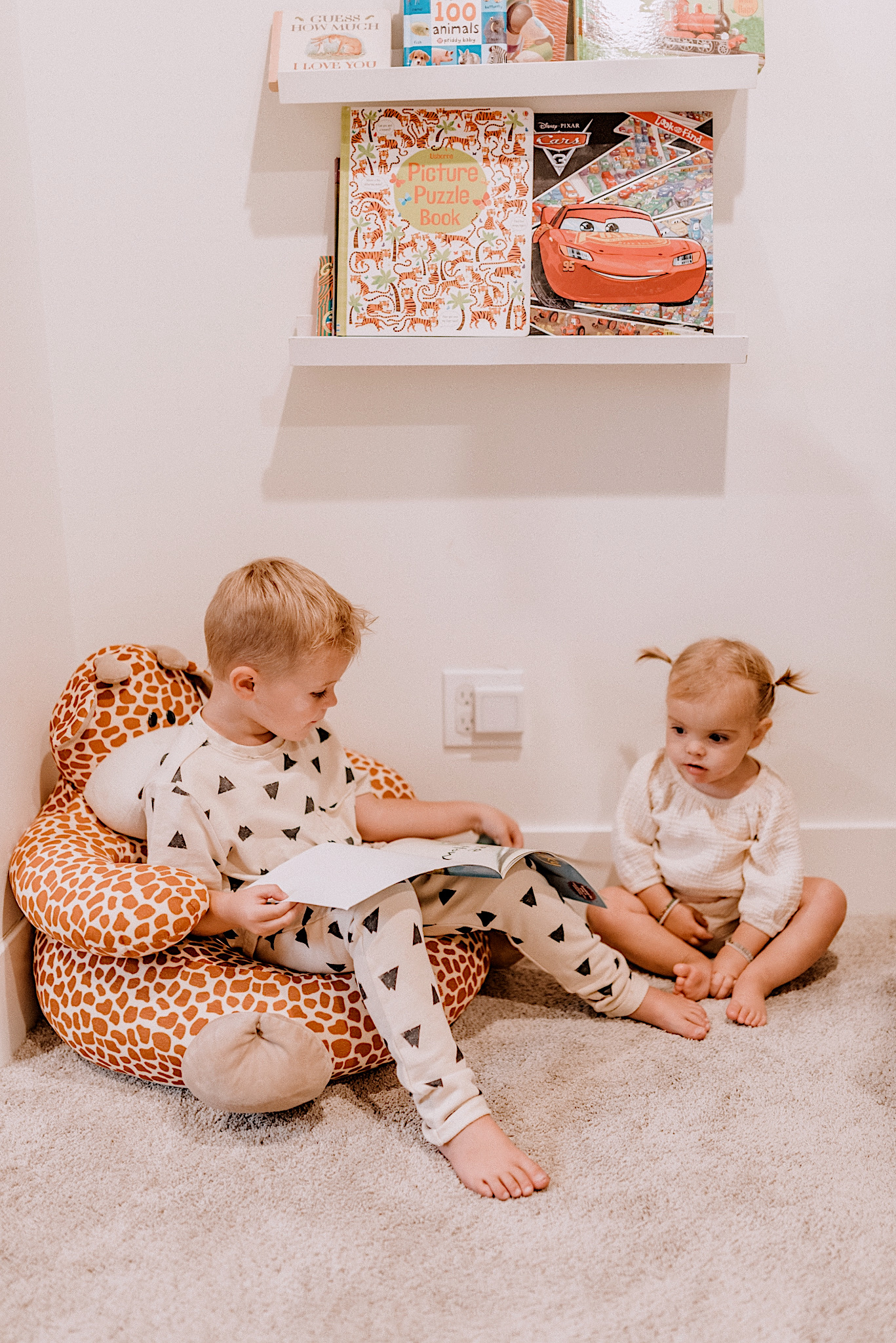 Best Children's Books by popular San Diego motherhood blog, Navy Grace: image of a little boy and little girl sitting on the floor and looking at books.