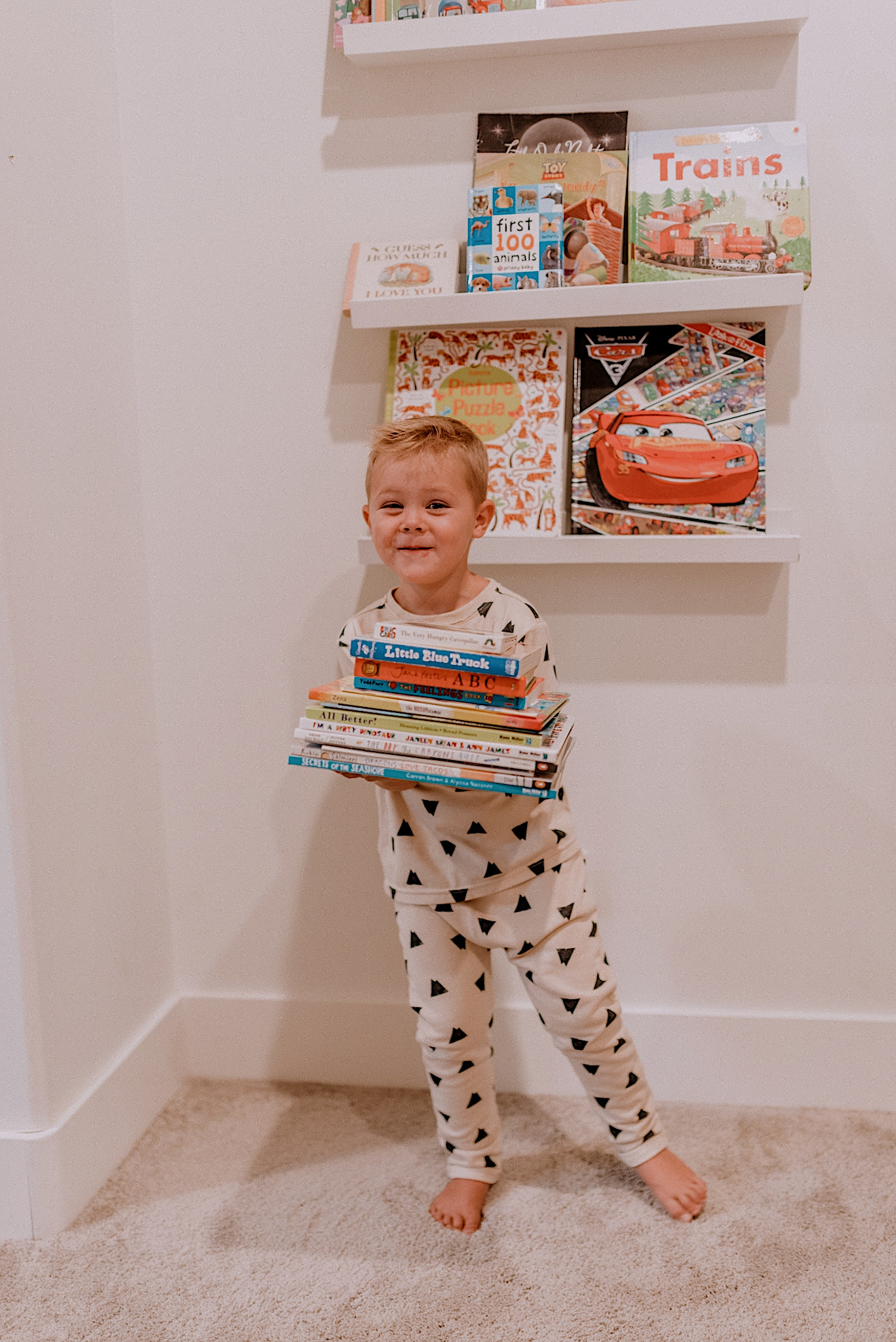 Best Children's Books by popular San Diego motherhood blog, Navy Grace: image of a little boy holding a stack of books.