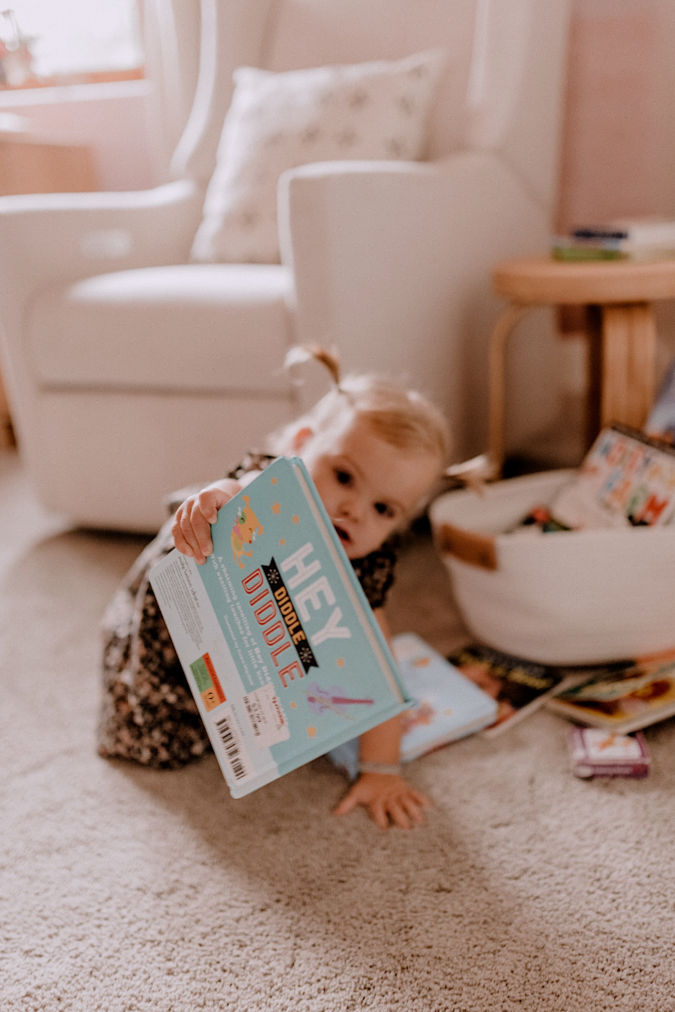 Best Children's Books by popular San Diego motherhood blog, Navy Grace: image of a a little girl sitting next to a white glider chair and looking at books in a white woven basket.