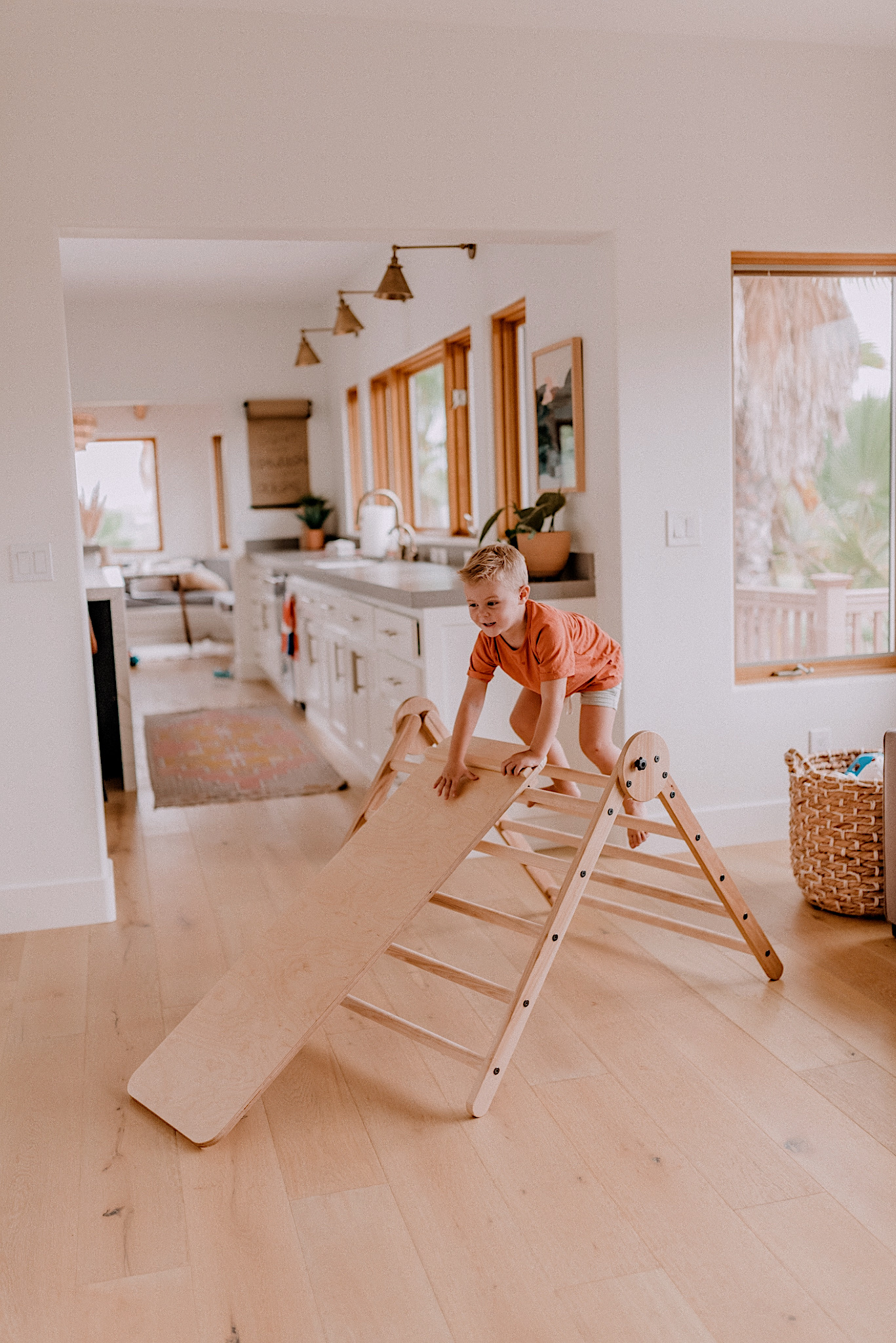 15 LEARNING ACTIVITIES FOR 3 TO 5 YEAR OLDS to try featured by top San Diego lifestyle blogger, Navy Grace | Learning Activities by popular San Diego motherhood blog, Navy Grace: image of a little boy playing on a Homi Baby Pikler Triangle Slide and Climbing Set.