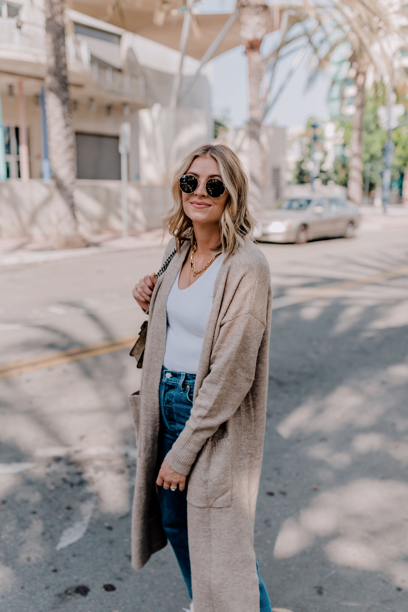 Long Cardigans by popular San Diego fashion blog, Navy Grace: image of a woman walking down a street and wearing a H&M long cardigan, Levi's Ribcage Ripped High Waist Ankle Straight Leg Jeans, Everlane The Long-Sleeve V-Neck Bodysuit, and Converse High Top Sneakers.