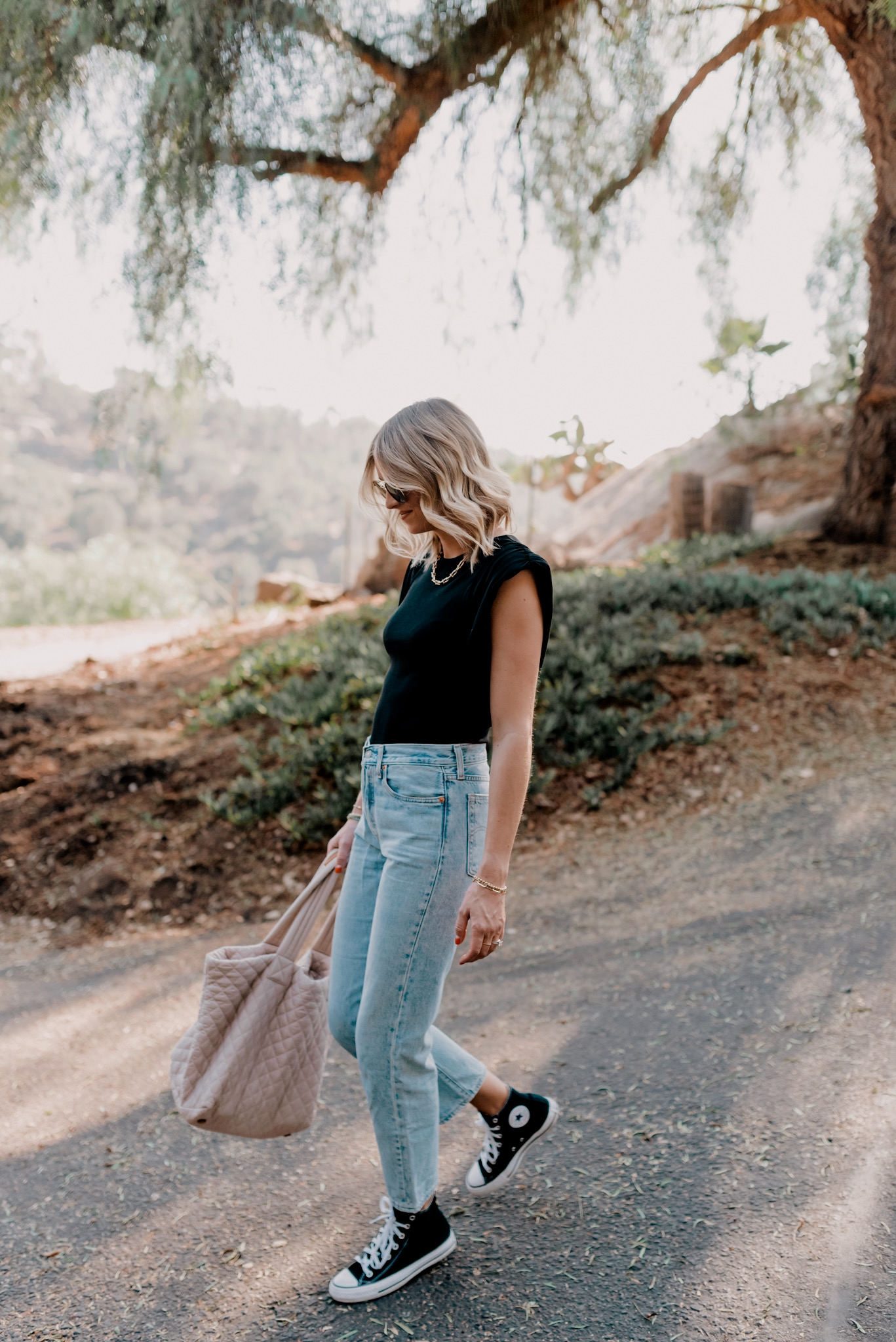 Top Sellers by popular San Diego fashion blog, Navy Grace: image of a woman wearing a Padded Cap Sleeve Crew Neck Thong Bodysuit, Urban Outfitters Levi's Wedgie Straight Jean, Converse high top sneakers, and carrying a MZ Wallace bag.