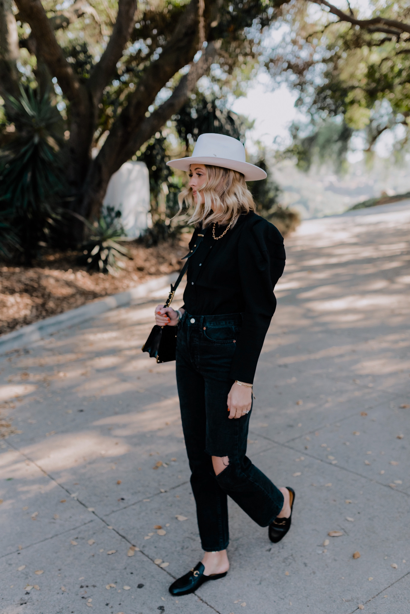 Black Clothing by popular San Diego fashion blog, Navy Grace: image of a woman walking outside and wearing a Express Puff Sleeve Button Front Top,Chicago Ripped Knee High Waist Dad Jeans TOPSHOP,Princetown Loafer Mule GUCCI, felt hat, and carrying a Prada Cashier shoulder bag.