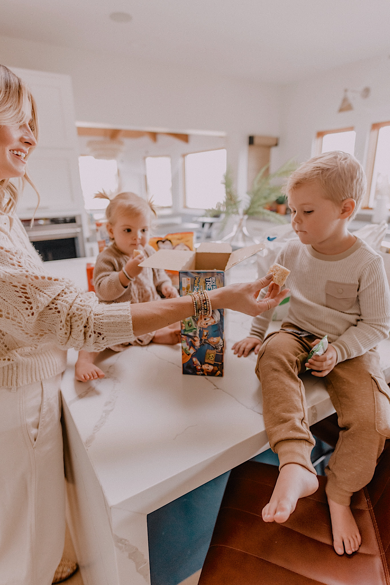 mom hacks saving money and time with walmart+ membership |mom hacks saving money and time with walmart+ membership | Walmart Membership by popular San Diego fashion blog, Navy Grace: image of a mom and her two kids standing around the kitchen island counter and eating rice krispy treats.