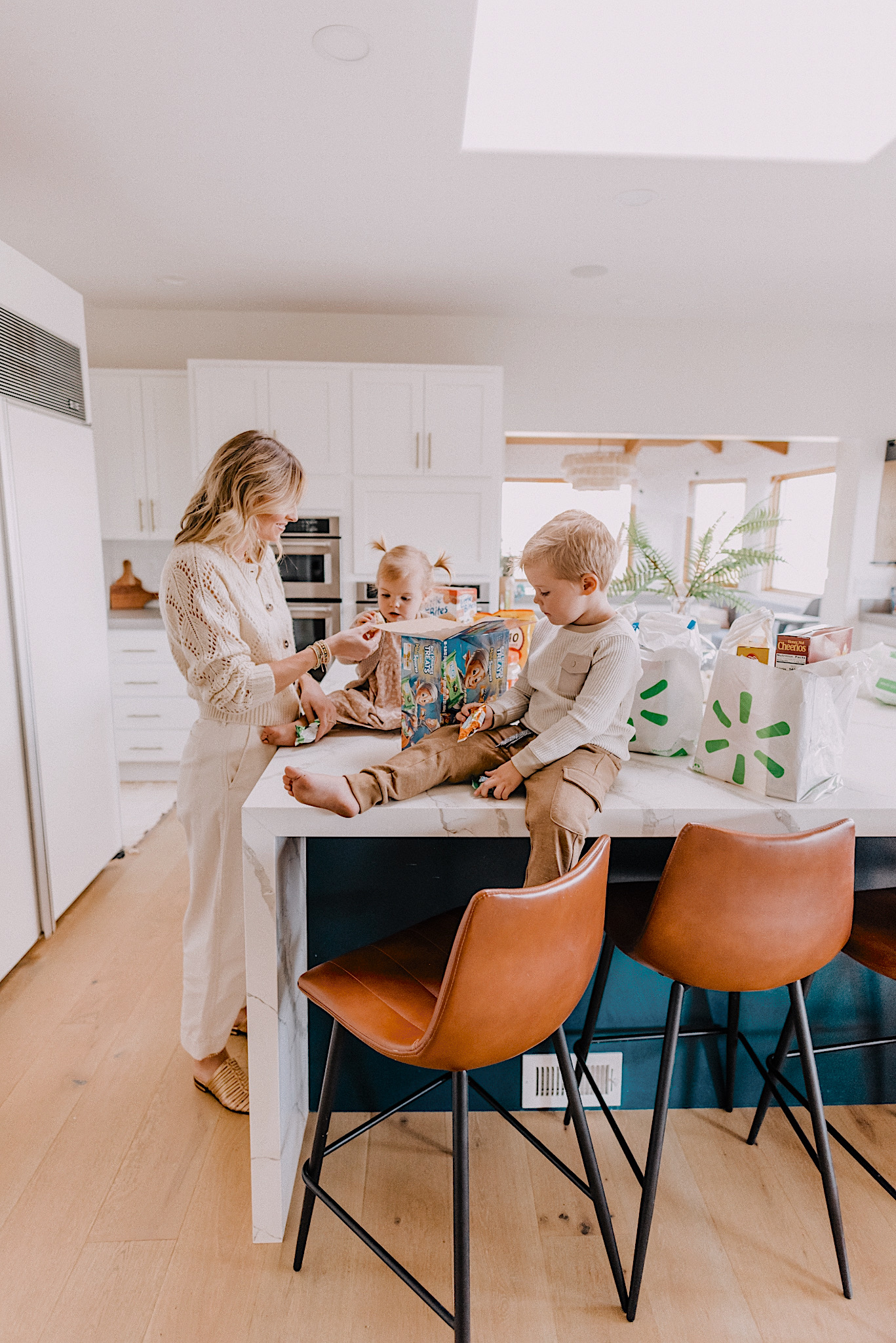 mom hacks saving money and time with walmart+ membership |Walmart Membership by popular San Diego fashion blog, Navy Grace: image of a mom and her two kids standing around the kitchen island counter and eating rice krispy treats.
