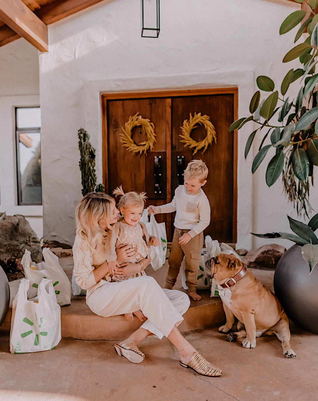 mom hacks saving money and time with walmart+ membership | Walmart Membership by popular San Diego fashion blog, Navy Grace: image of a mom, her two kids, and her do sitting outside on their front steps next to some Walmart grocery bags.