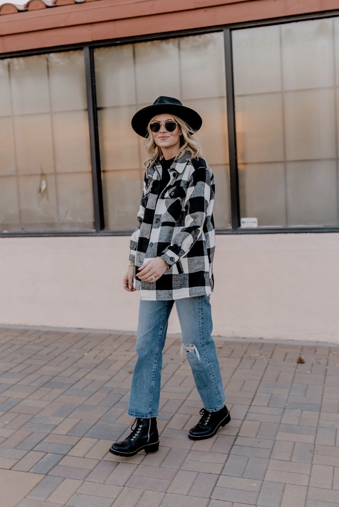 Shirt Jackets by popular San Diego fashion blog, Navy Grace: image of a woman standing outside and wearing a black and white buffalo plaid shirt jacket, Free People Levi's ribcage denim,AQUA Women's Jax Combat Boots, Free PeopleModern Turtleneck Top, and Ray-Ban sunglasses.